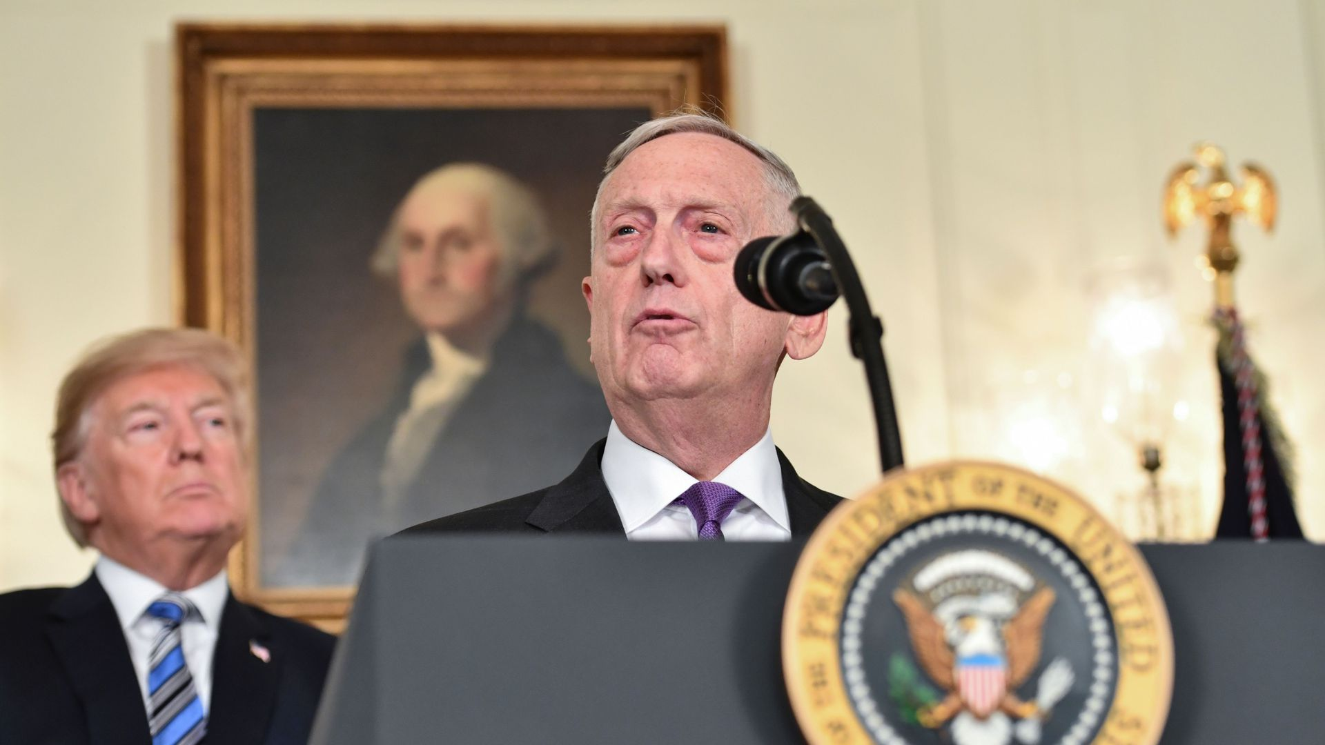 President Trump looks with concern at Secretary of Defense Jim Mattis as Mattis speaks at a podium.