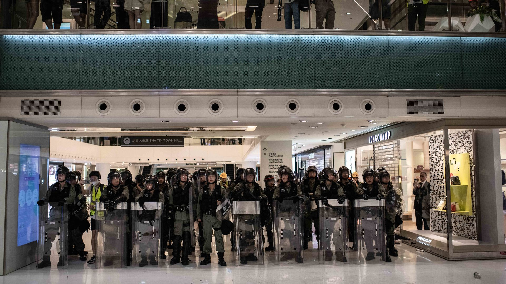 In this image, a line of riot police stand in a strip mall