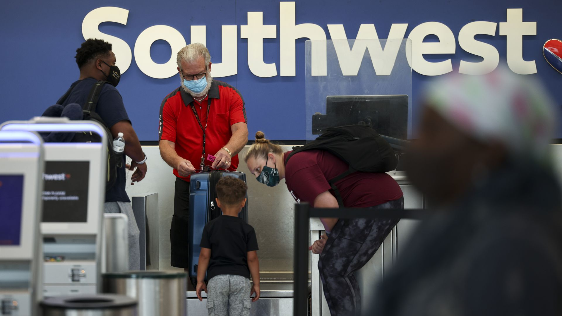 At an airport check-in desk, a masked Southwest employee helps two masked men and a little boy.