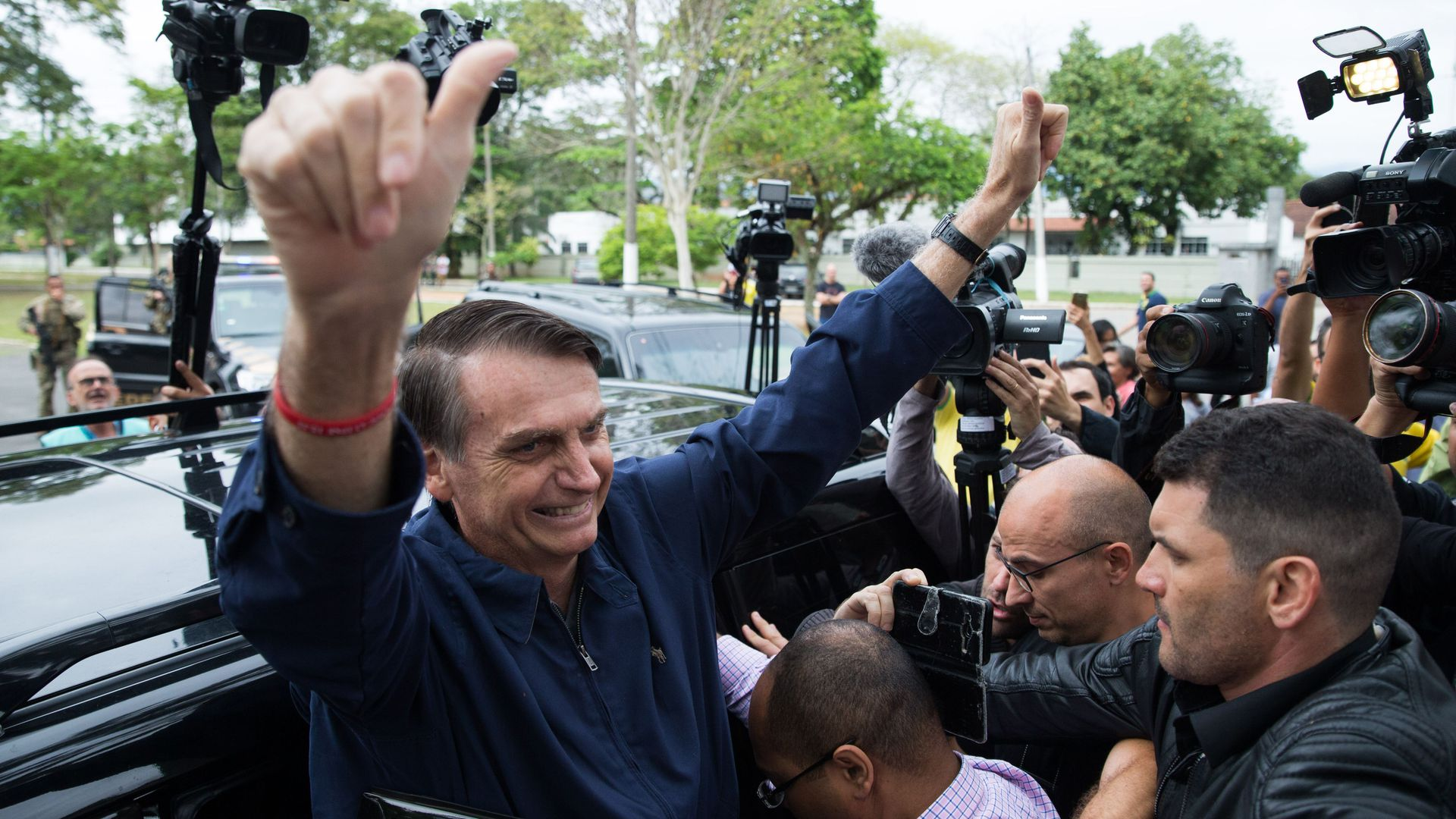 Jair Bolsonaro gets out of car, puts arms and thumbs up while surrounded by people