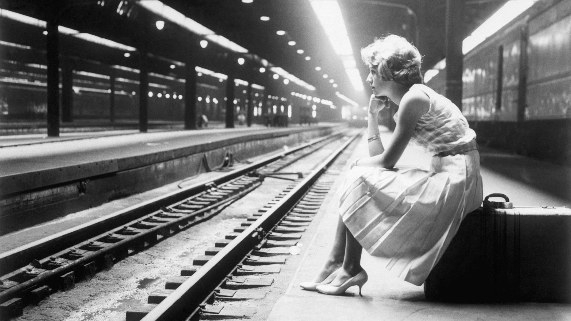 Black and white photo of a woman sitting on a suitcase on a train platform