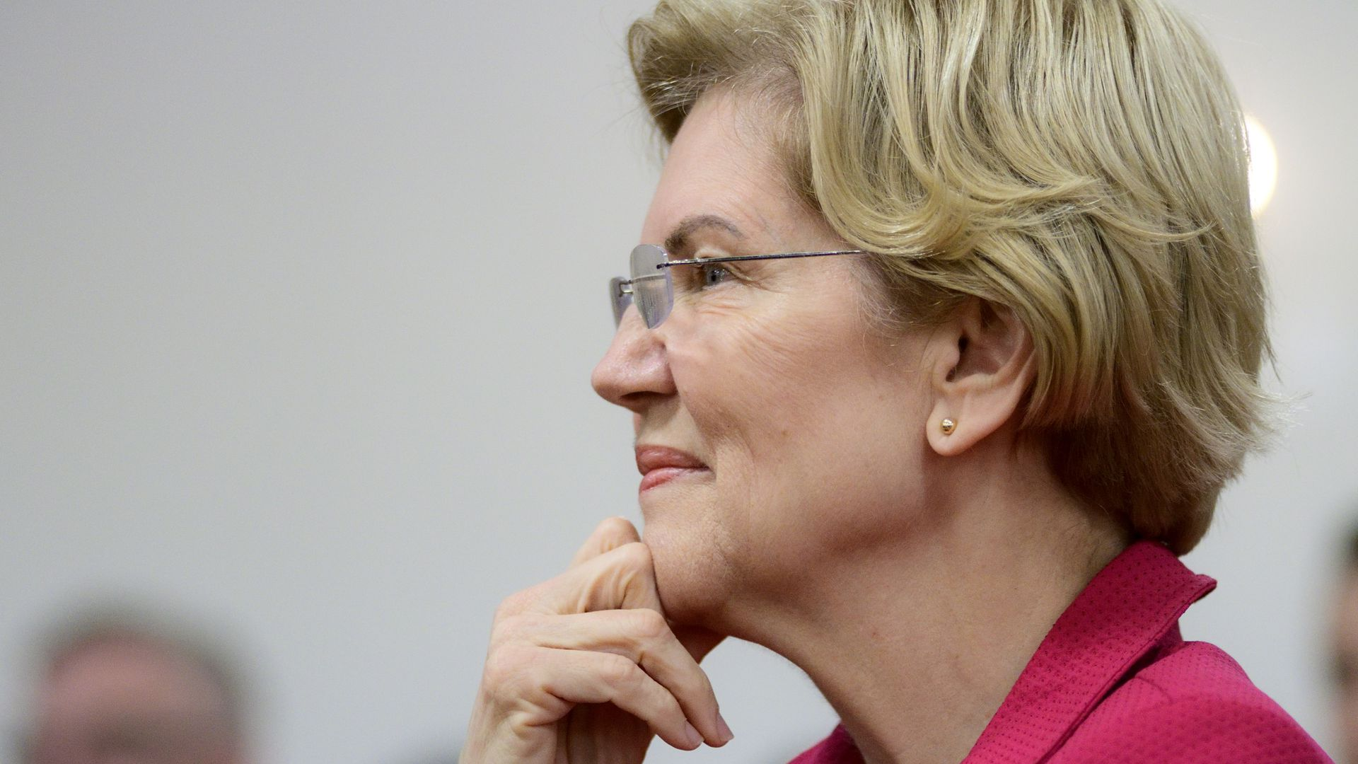 Warren smiling while touching her hand to her face. She is wearing a pink blazer-looking jacket and glasses.