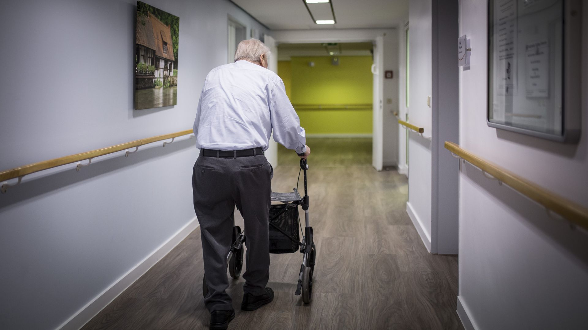 Old man with a walker walking away from camera