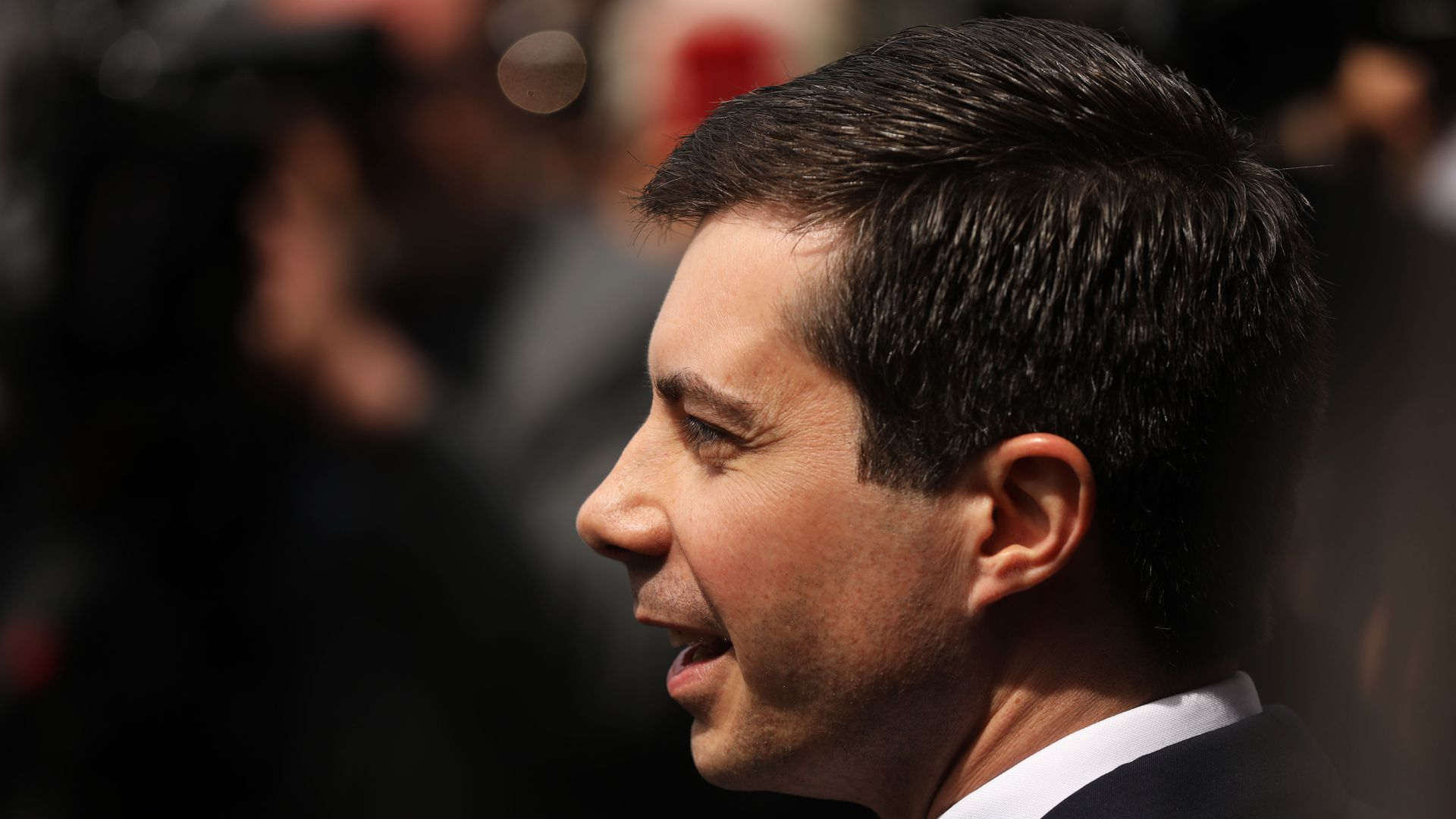 This image is a profile view of Pete Buttigieg, who stands and walks in a suit.