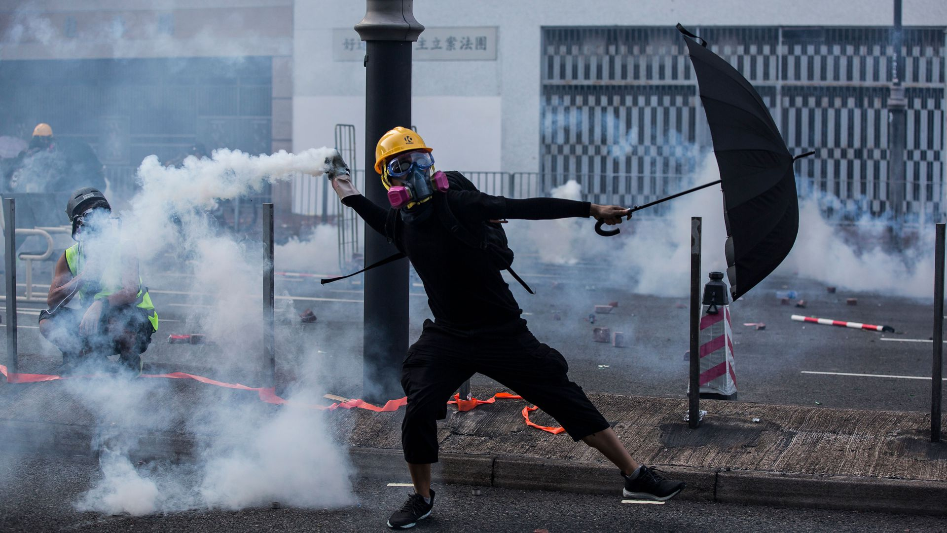 Photo of a protester with an umbrella on Hong Kong street bathed in tear gas