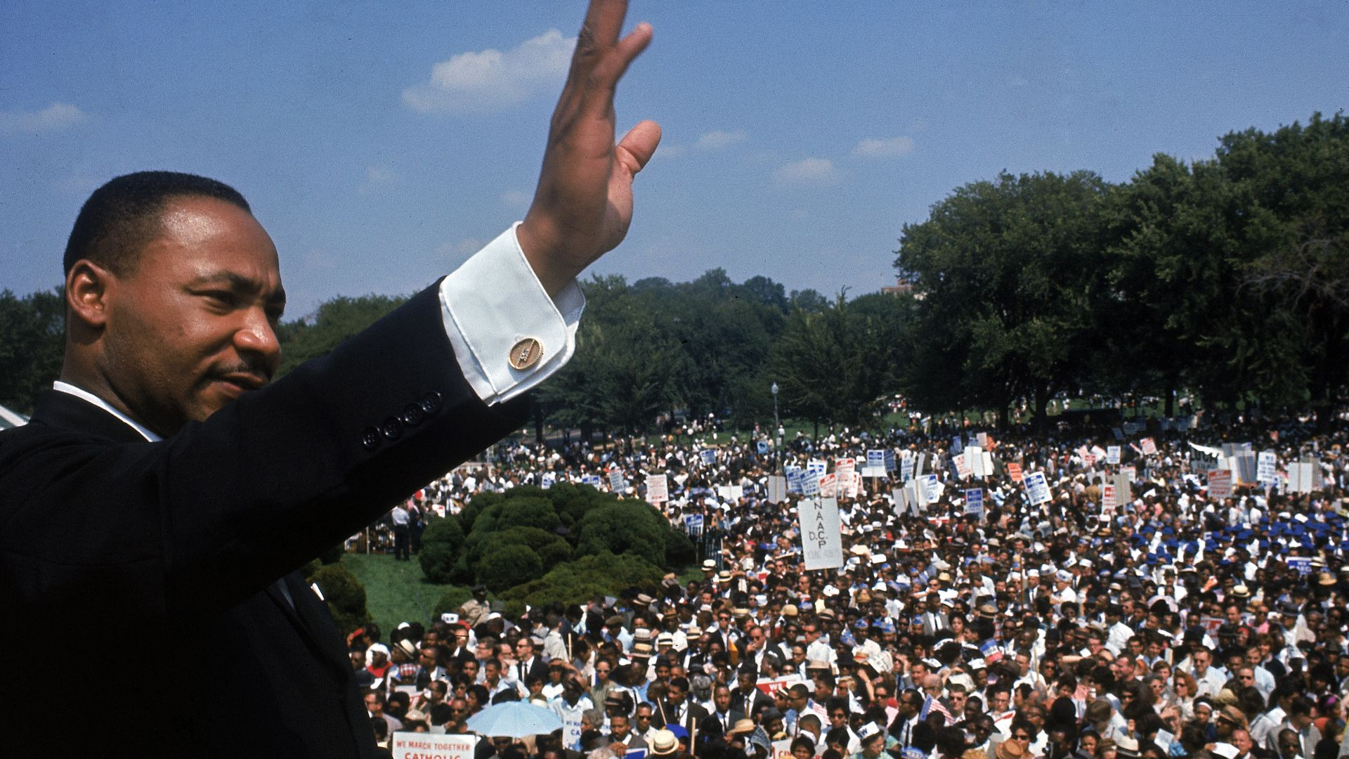 Martin Luther King, Jr. waves to a crowd