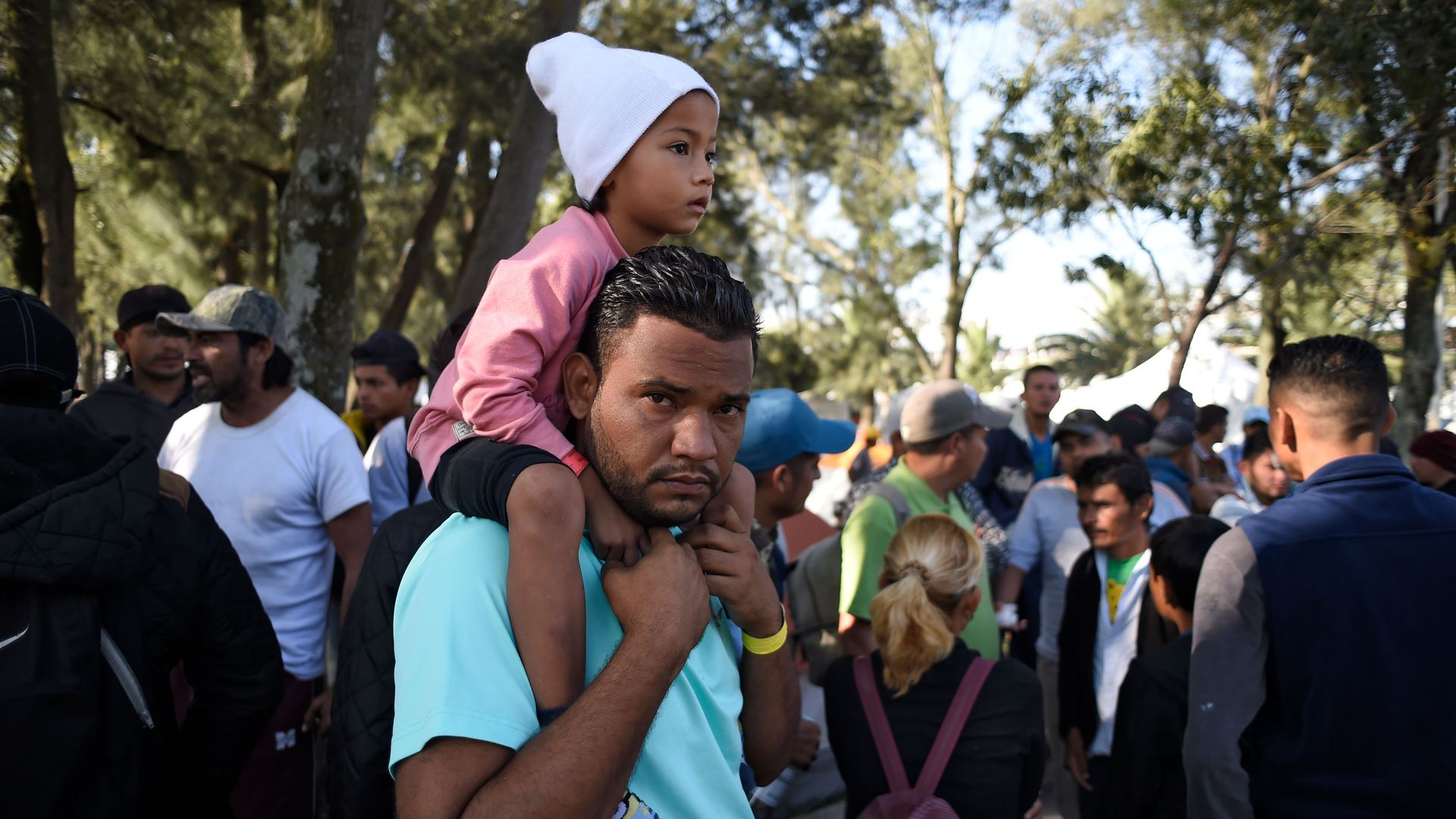 A migrant child sits on her father's shoulder