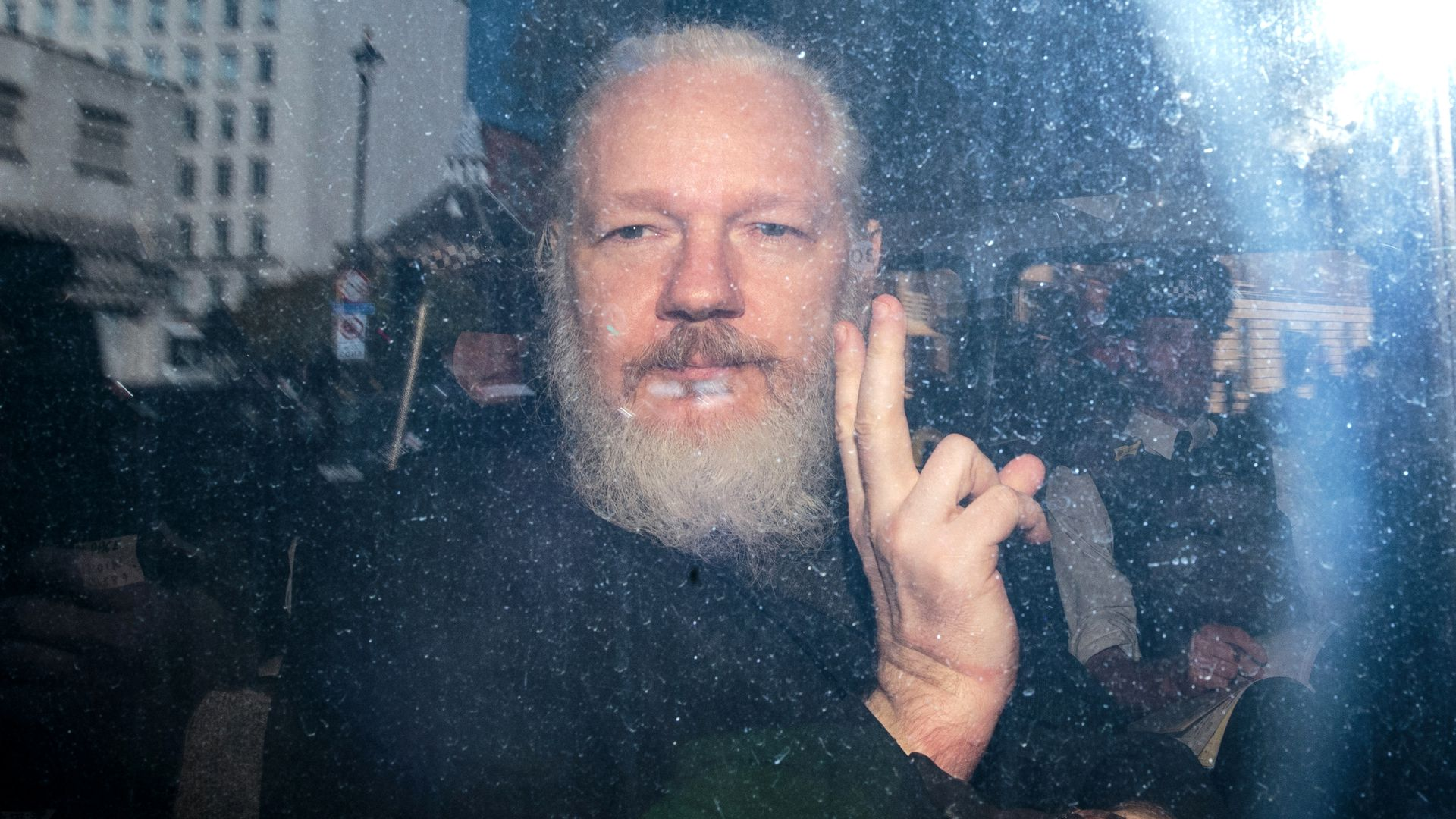 Assange makes a peace sign at the camera in this image.
