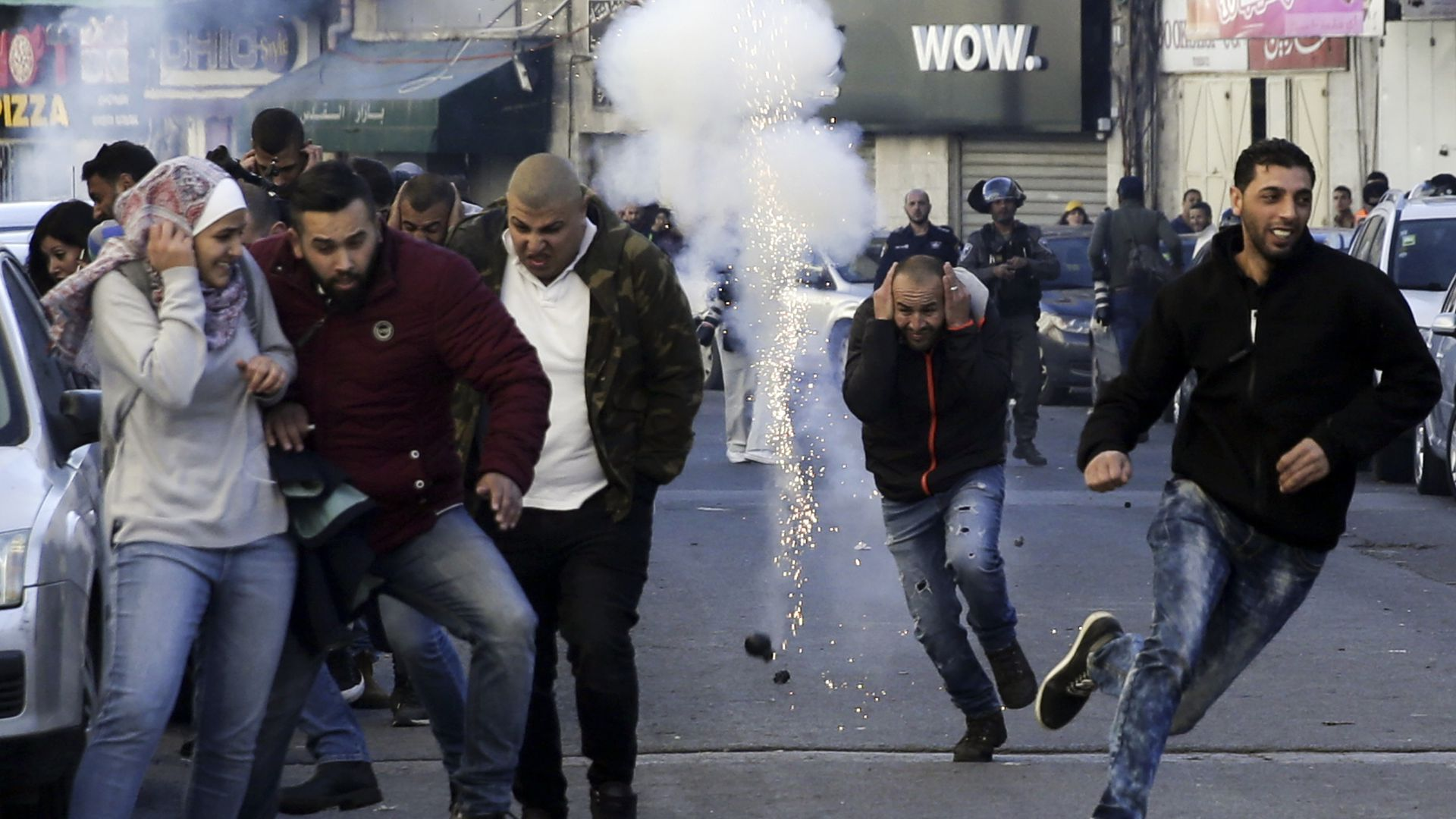 Palestinians run away from a sound bomb during clashes with Israeli security forces.