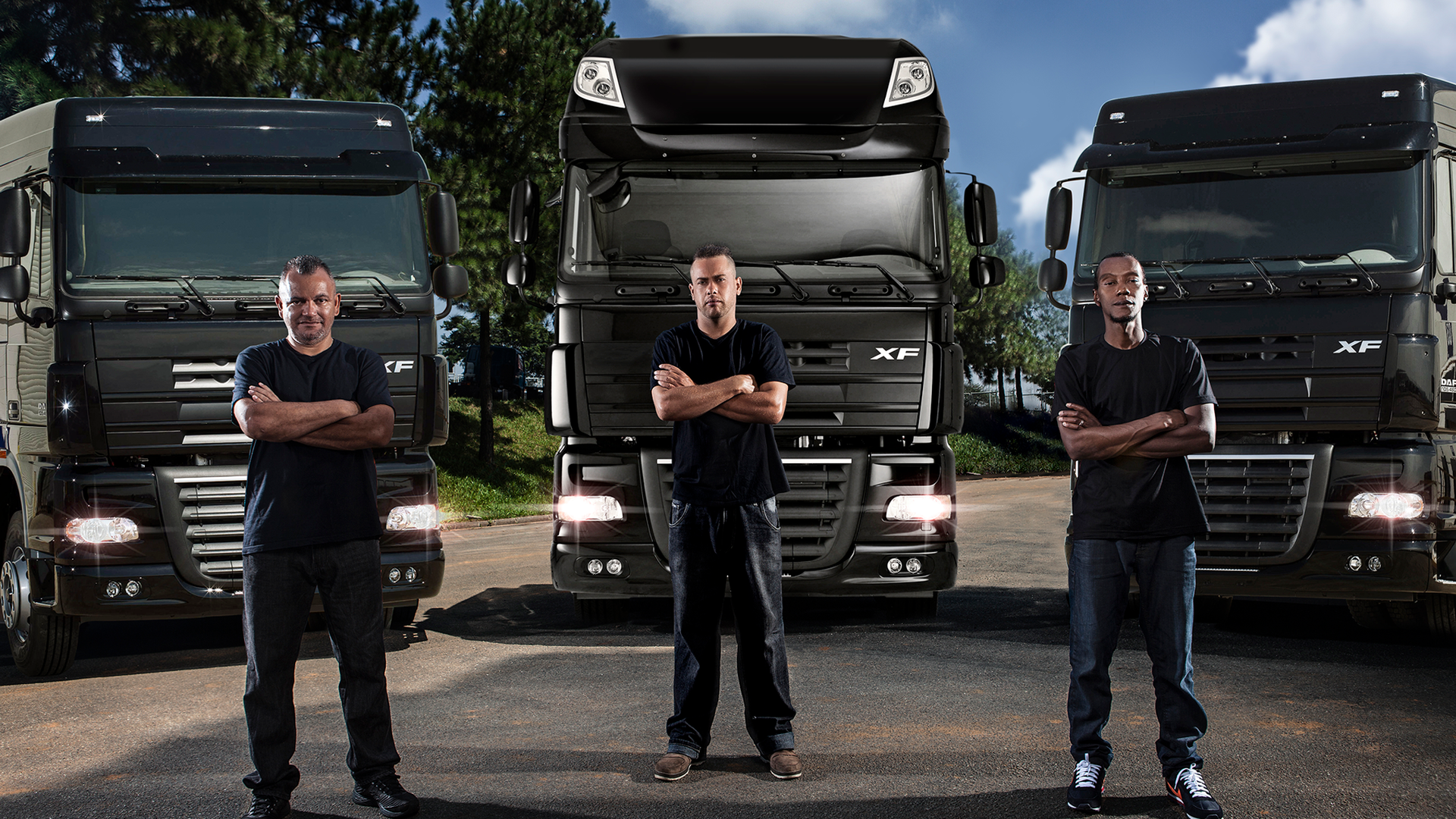 Three men stand in front of their trucks.