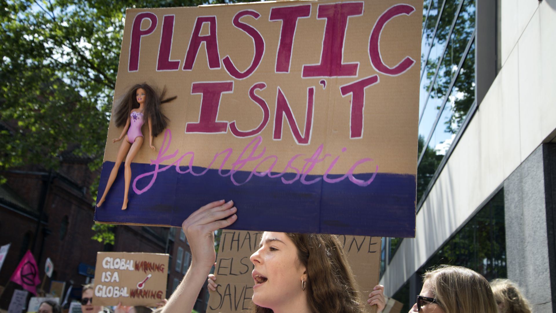 A girl holds a sign with a Barbie doll which says 'Plastic is not fantastic'.