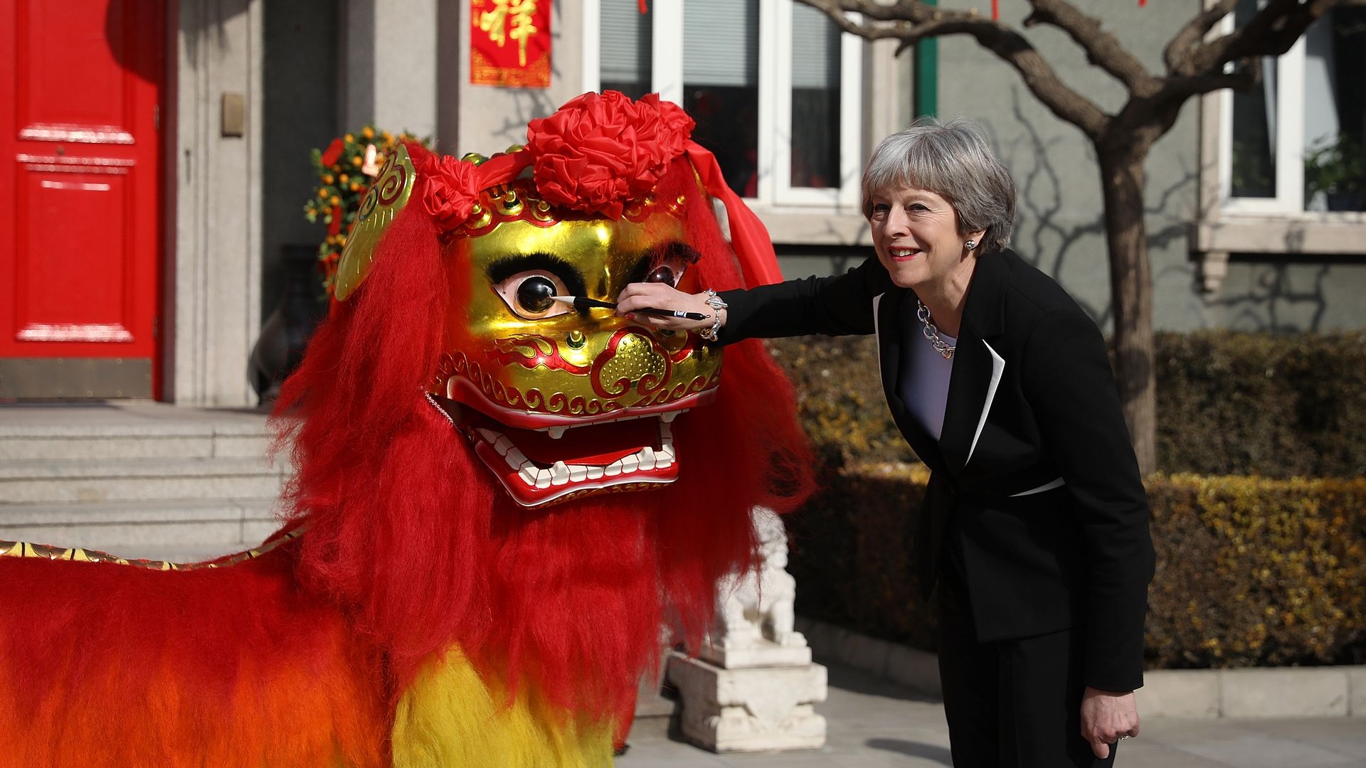 Theresa May touches a Chinese dragon