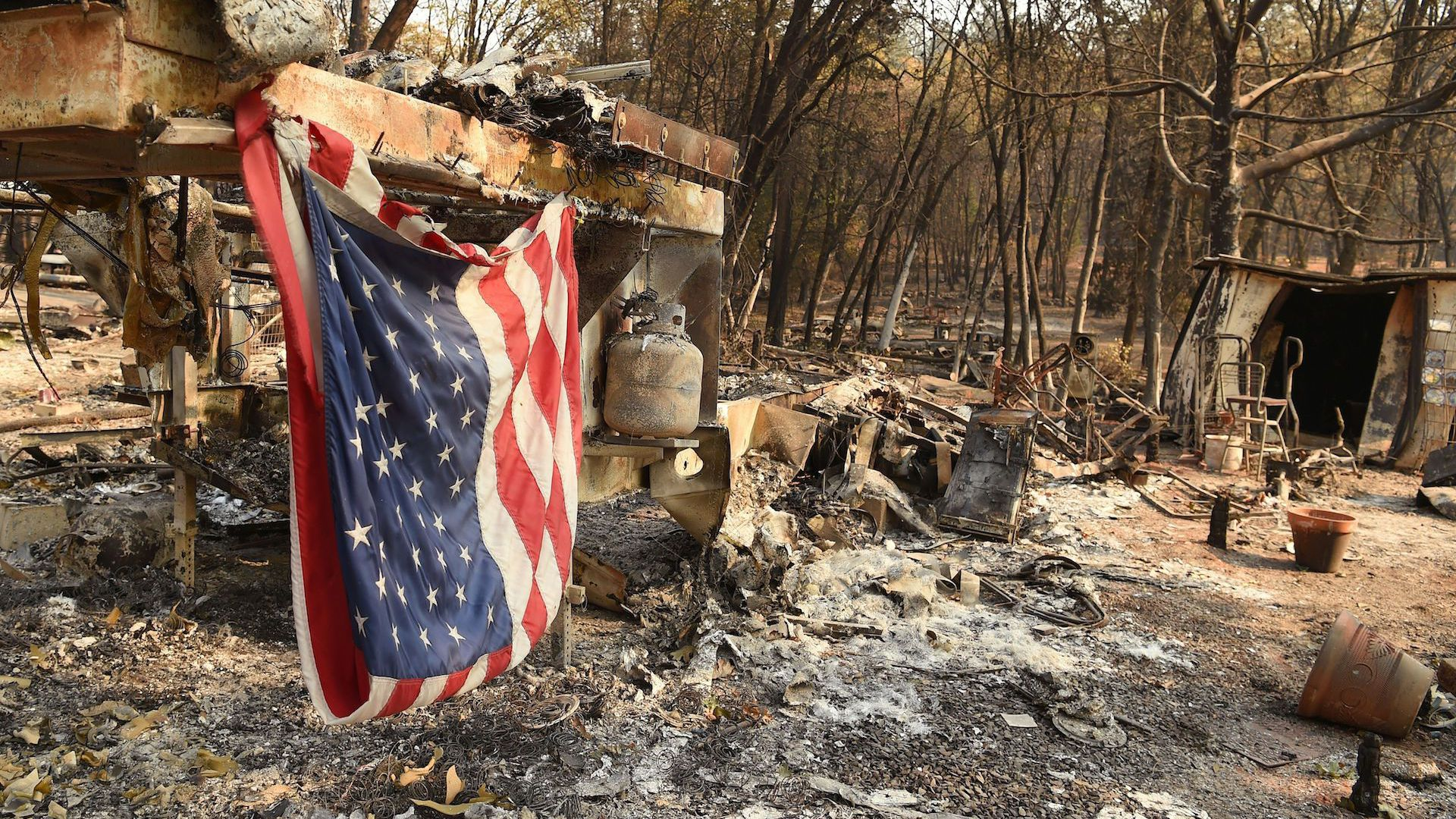 An American flag hangs at a burned out mobile home park