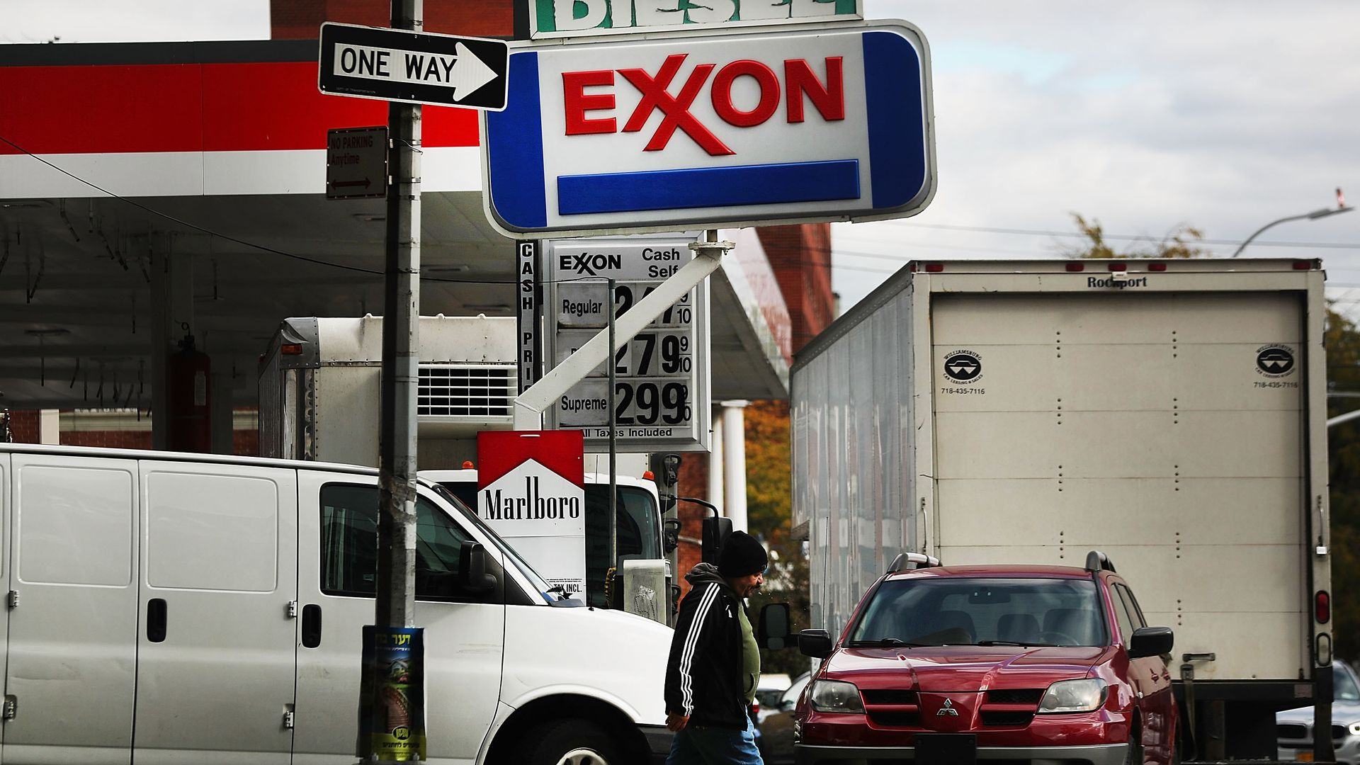 In this image, a man walks underneath an Exxon sign at a gas station.