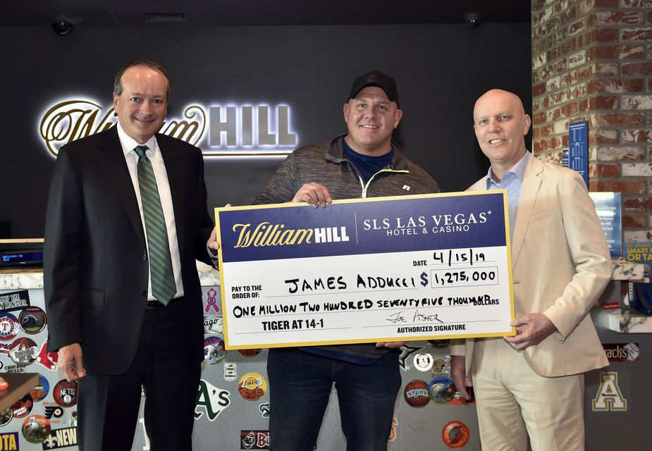 William Hill US CEO Joe Asher (left), James Adducci and SLS Las Vegas general manager Paul Hobson (right) stand with a ceremonial check of Adducci's winnings.