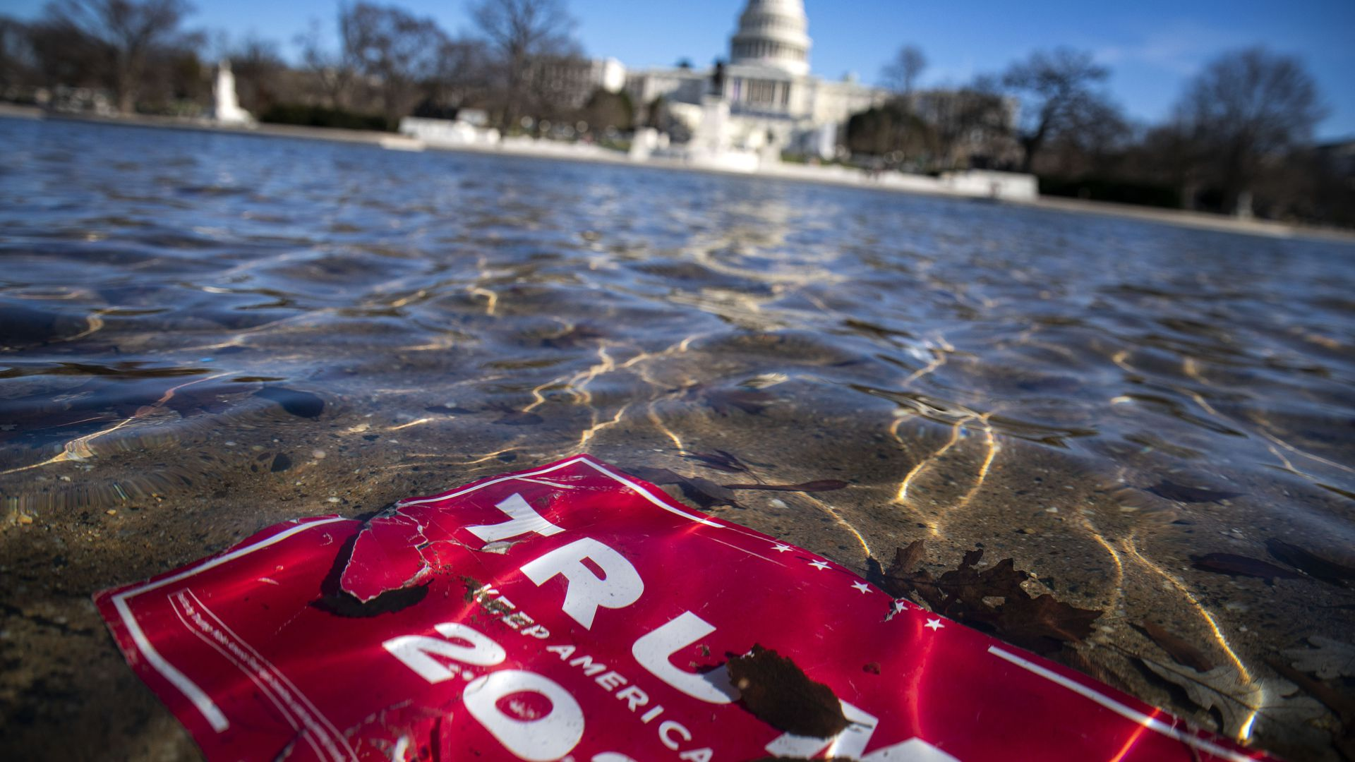 Trump campaign sign floats in river near the Capitol building.