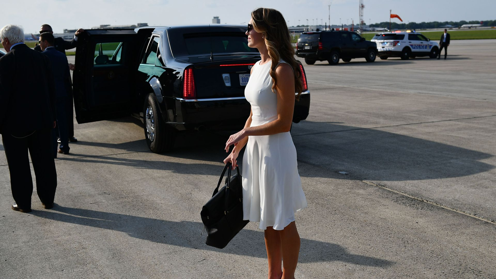 Hope Hicks stands outside wearing a white dress, heels and sunglasses