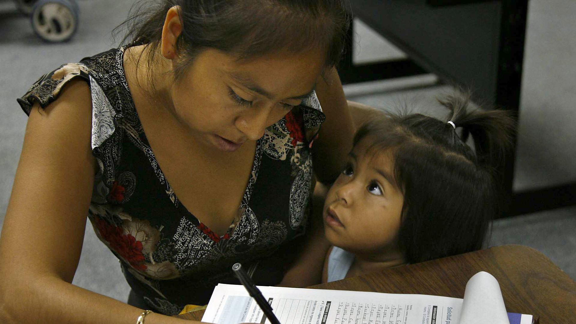 A woman and her child fill out an application for food stamps.