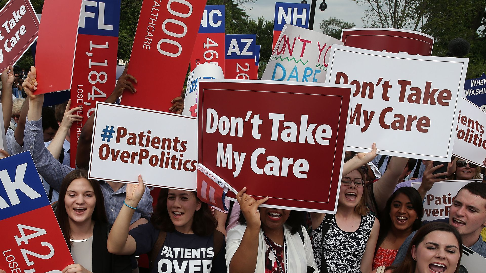 Protester hold signs outside of the Supreme Court during an Affordable Care Act case.