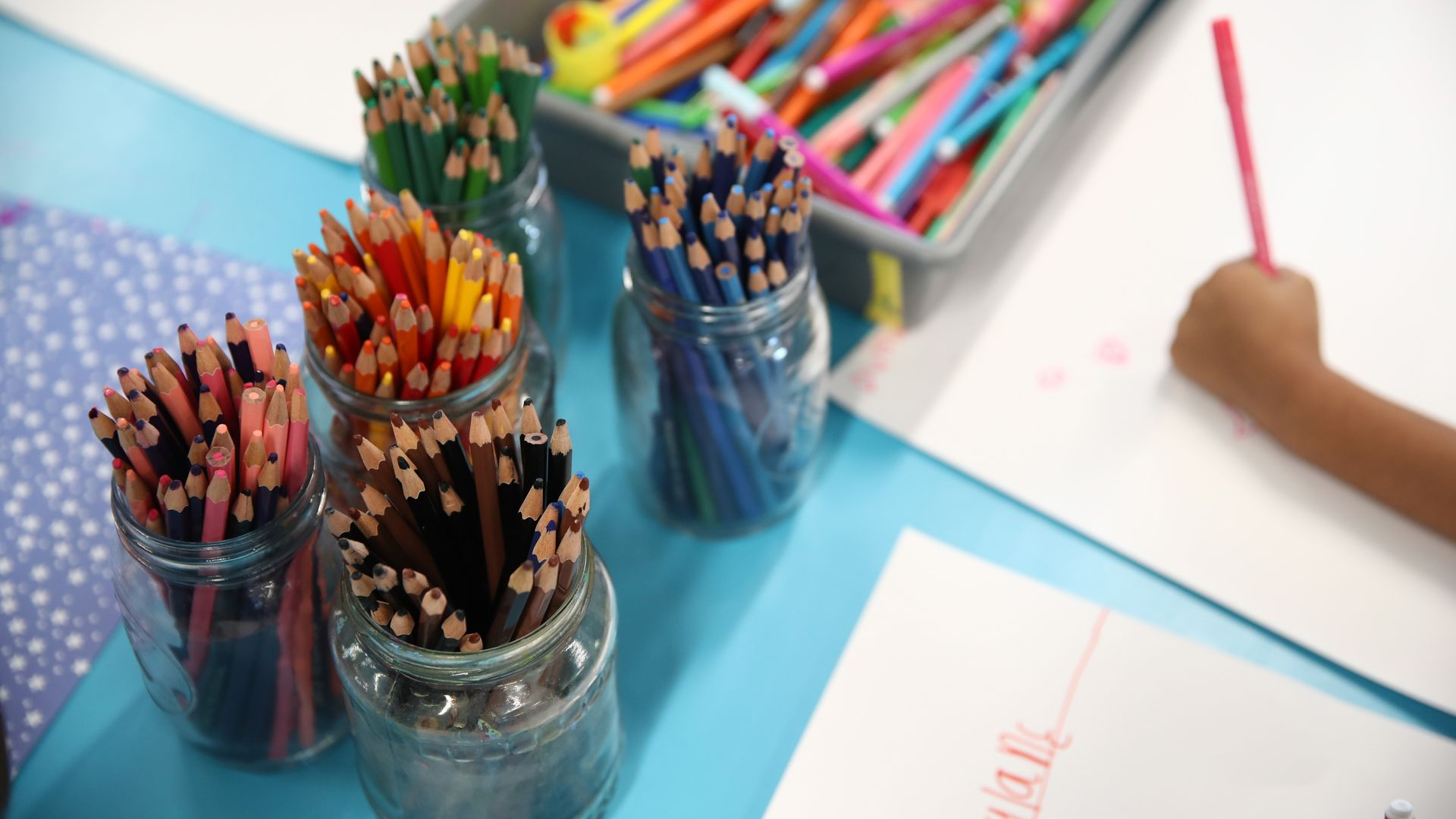 Piles of colored pencils are shown on a desk next to a child coloring