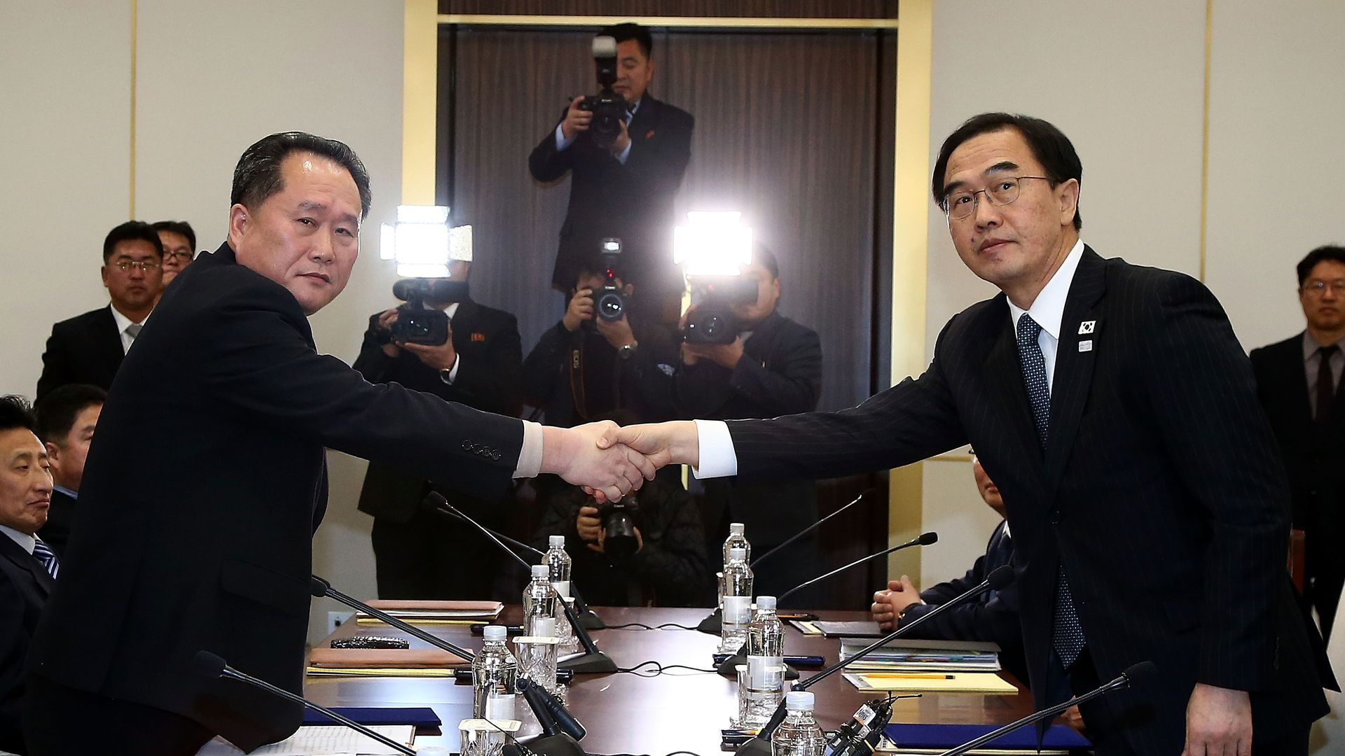 North Korea and South Korea delegation shake hands in Panmunjom.