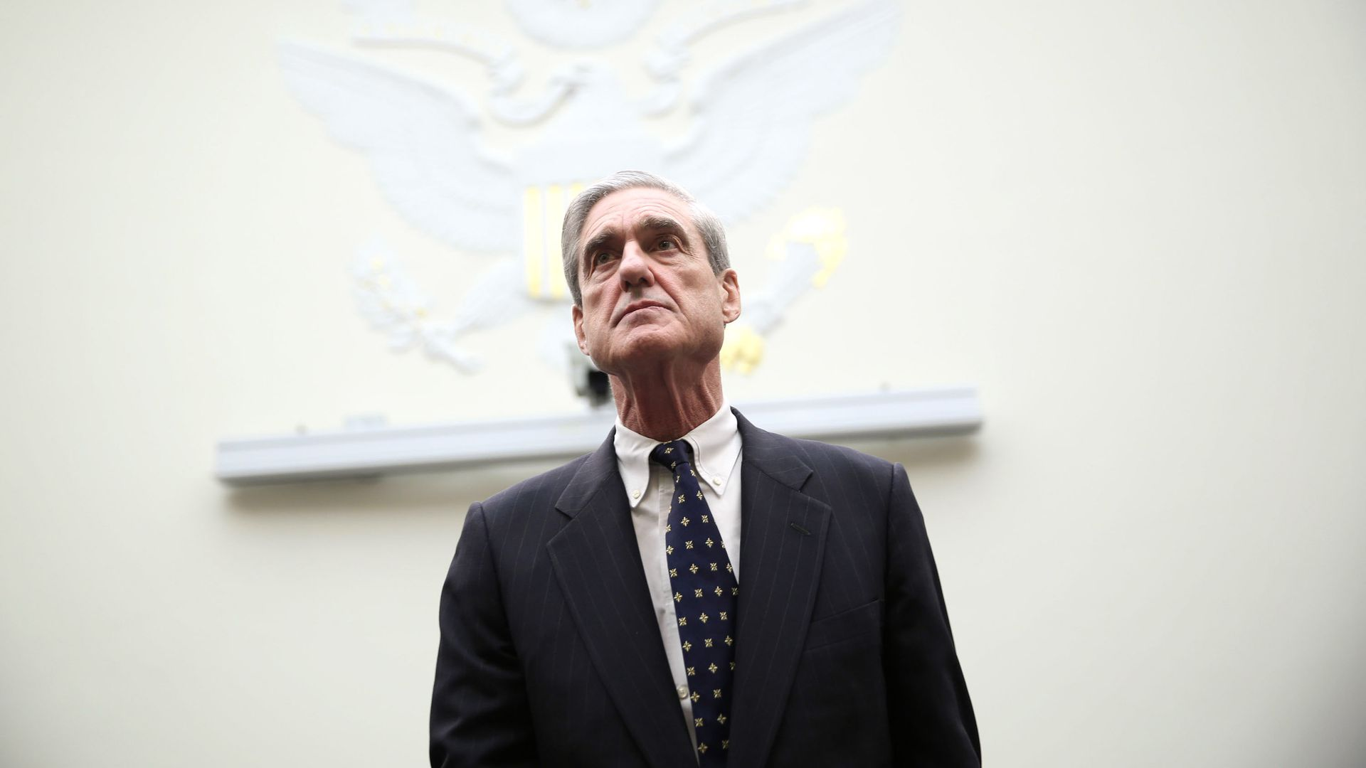 In this image, special counsel Robert Mueller stands in front of a white background.