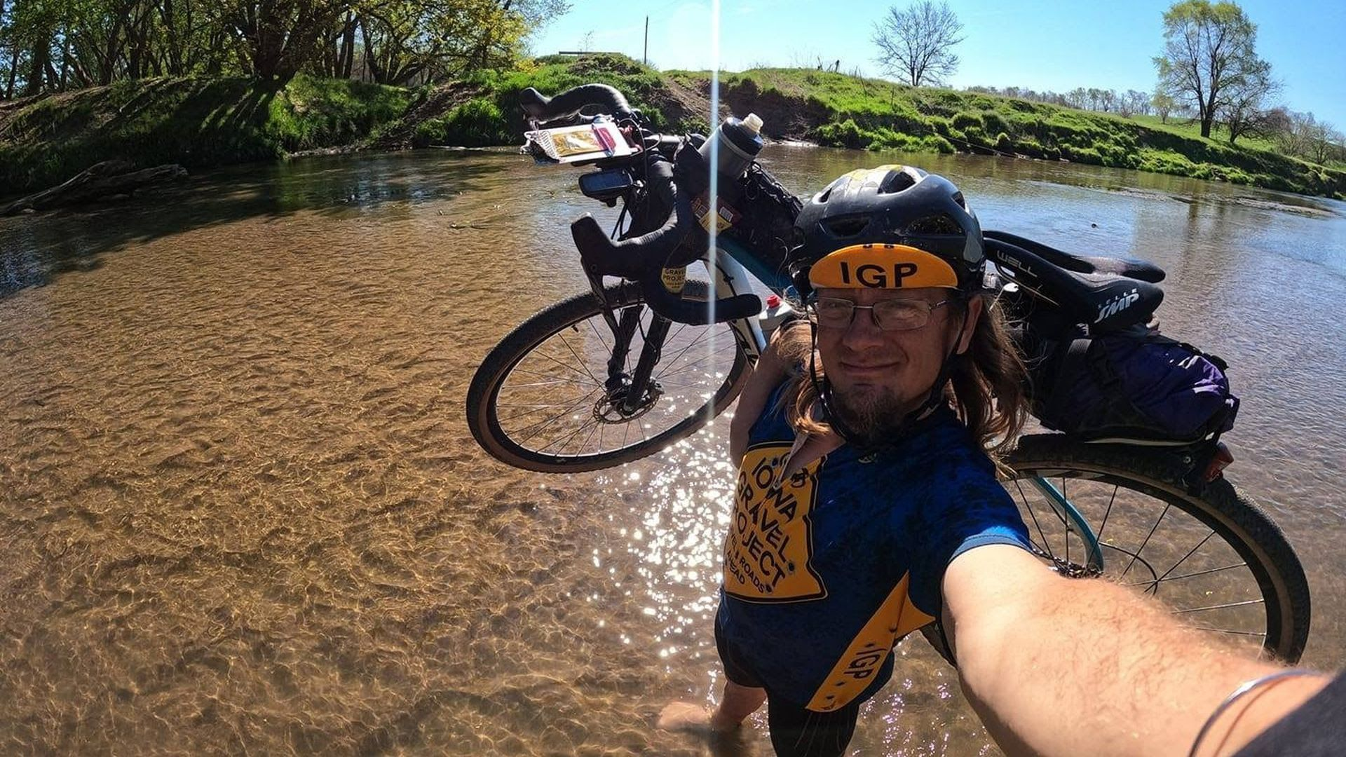 Cole Ledbetter takes a selfie with his bike on his shoulder, while standing in a pond.