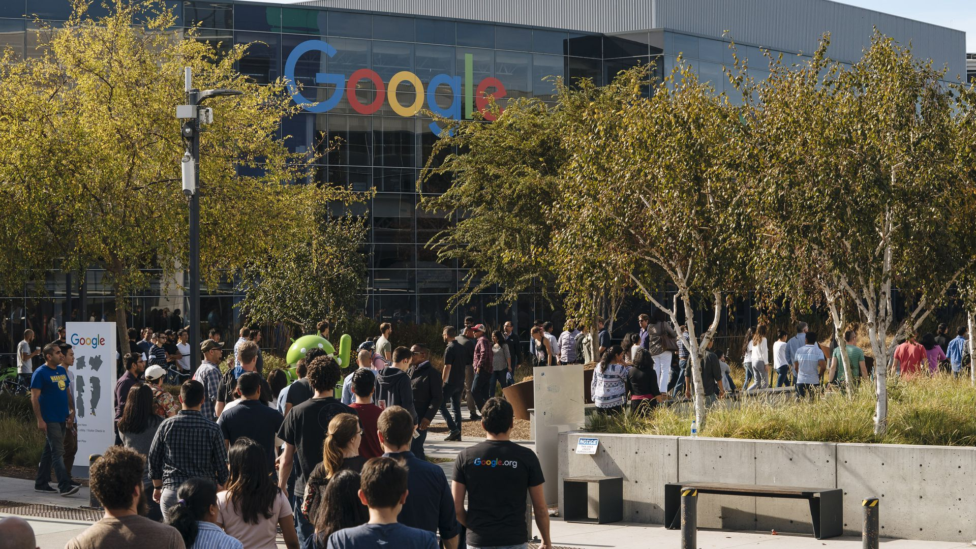 In this image, a large crowd of people walk towards a Google office during a walkout protest