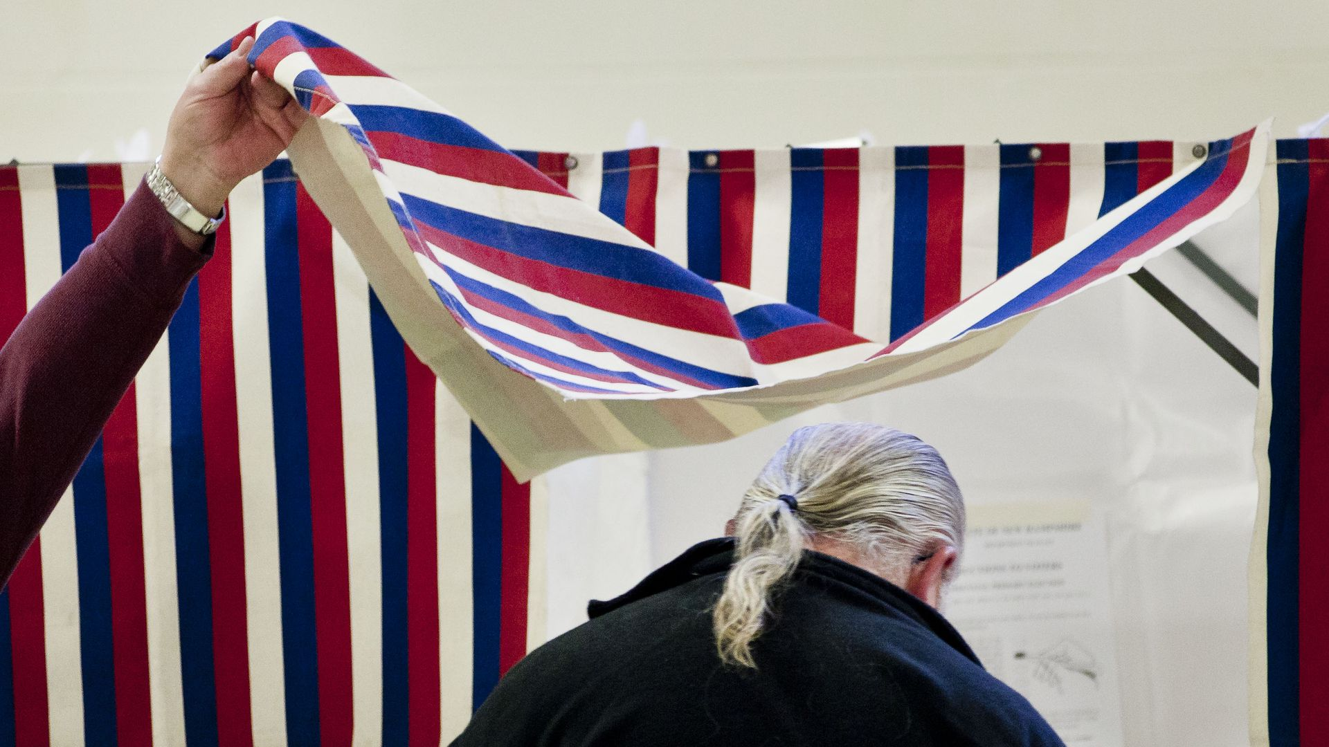 Someone lifts the red, white, and blue curtain as a man enters a polling booth