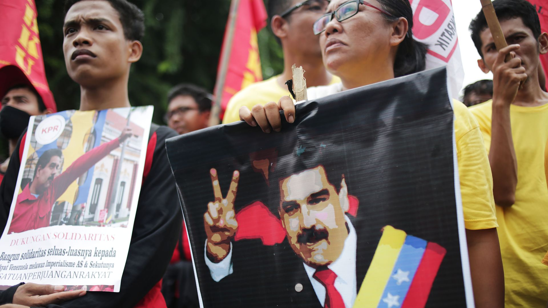 In this picture, a Venezuelan woman holds a banner of President Maduro at a protest.