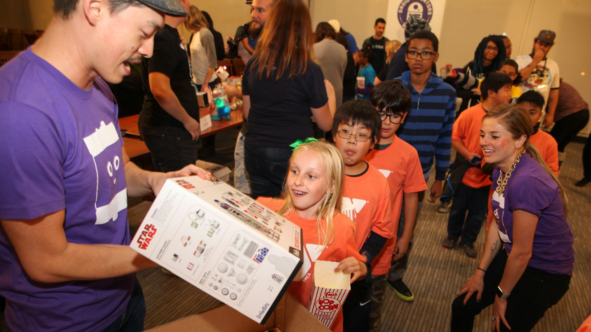In this image, a man hands out toy building and code kits to a line of children. The first child in line is a young blonde girl.