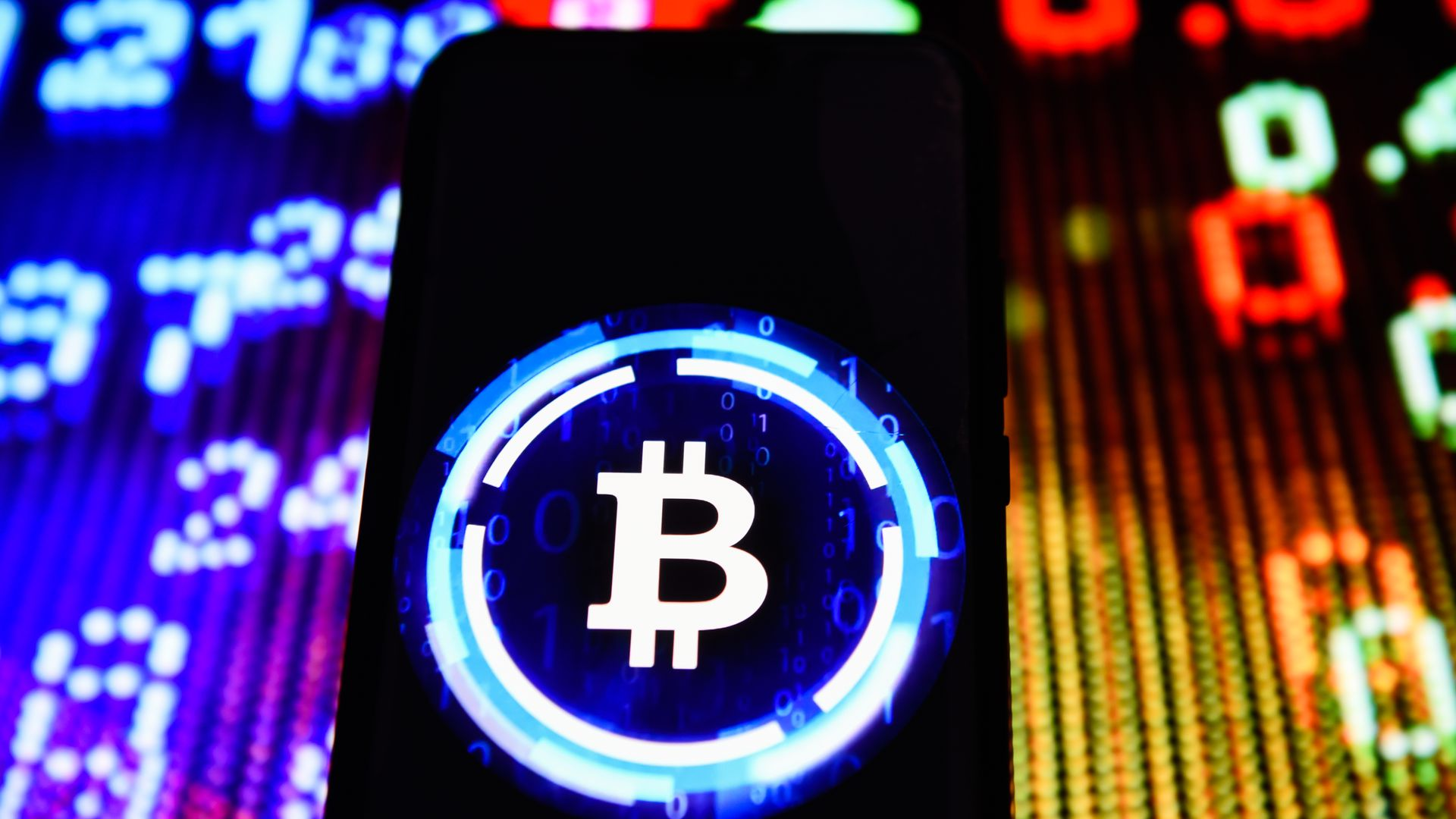 In this image, the neon blue and white Bitcoin logo is highlighted on a black phone screen in front of a bright colored background of numbers.