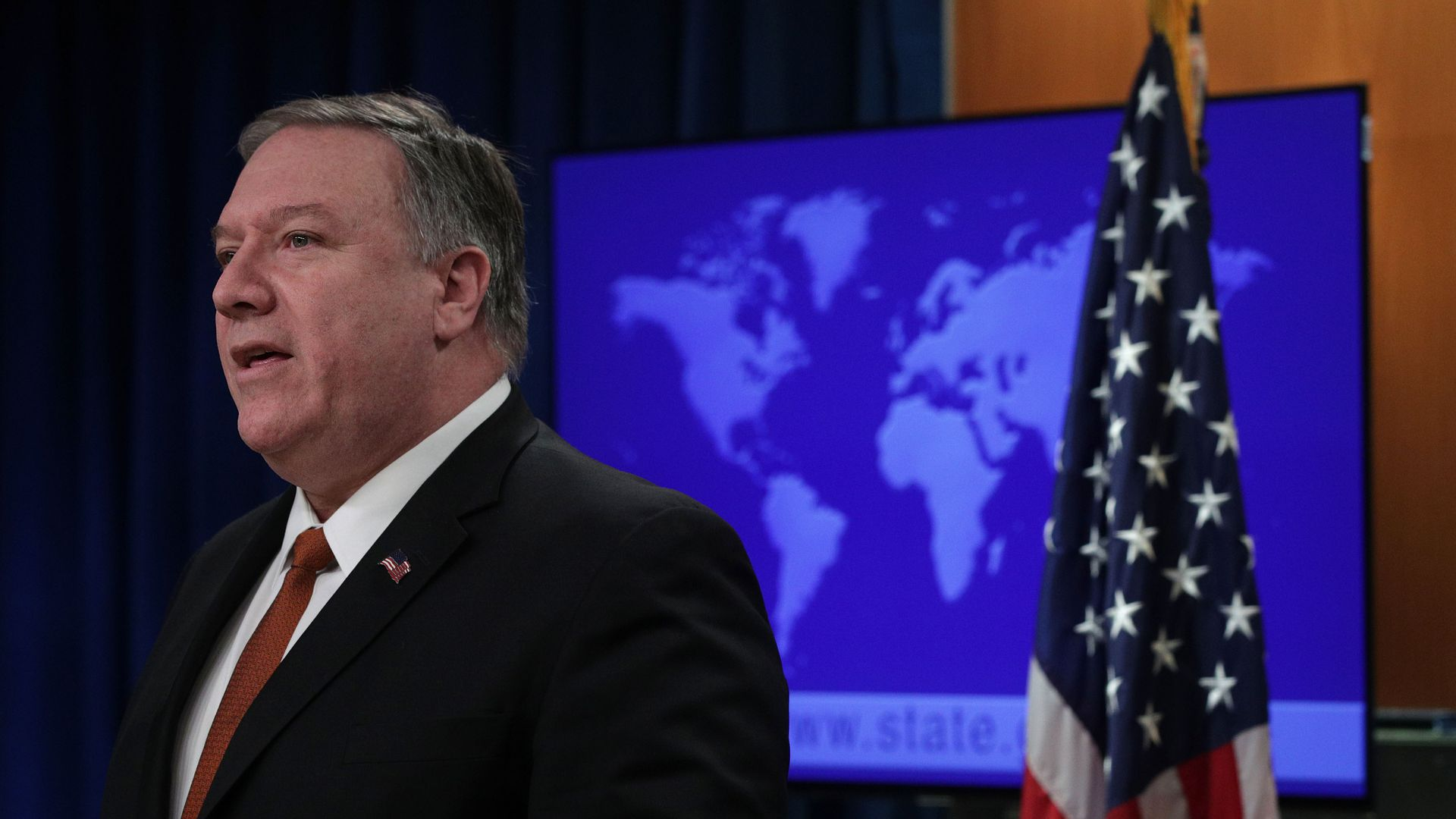 Mike Pompeo is pictured standing next to the American flag.