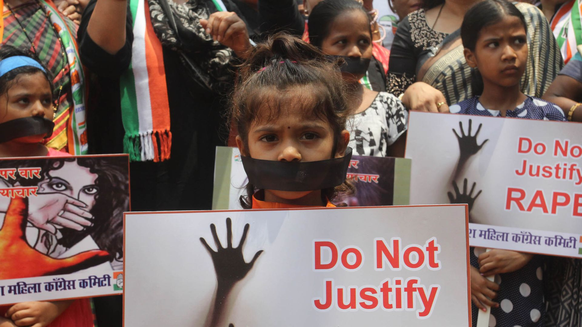 "A young girl holds a sign that reads ""Do not justify rape."""
