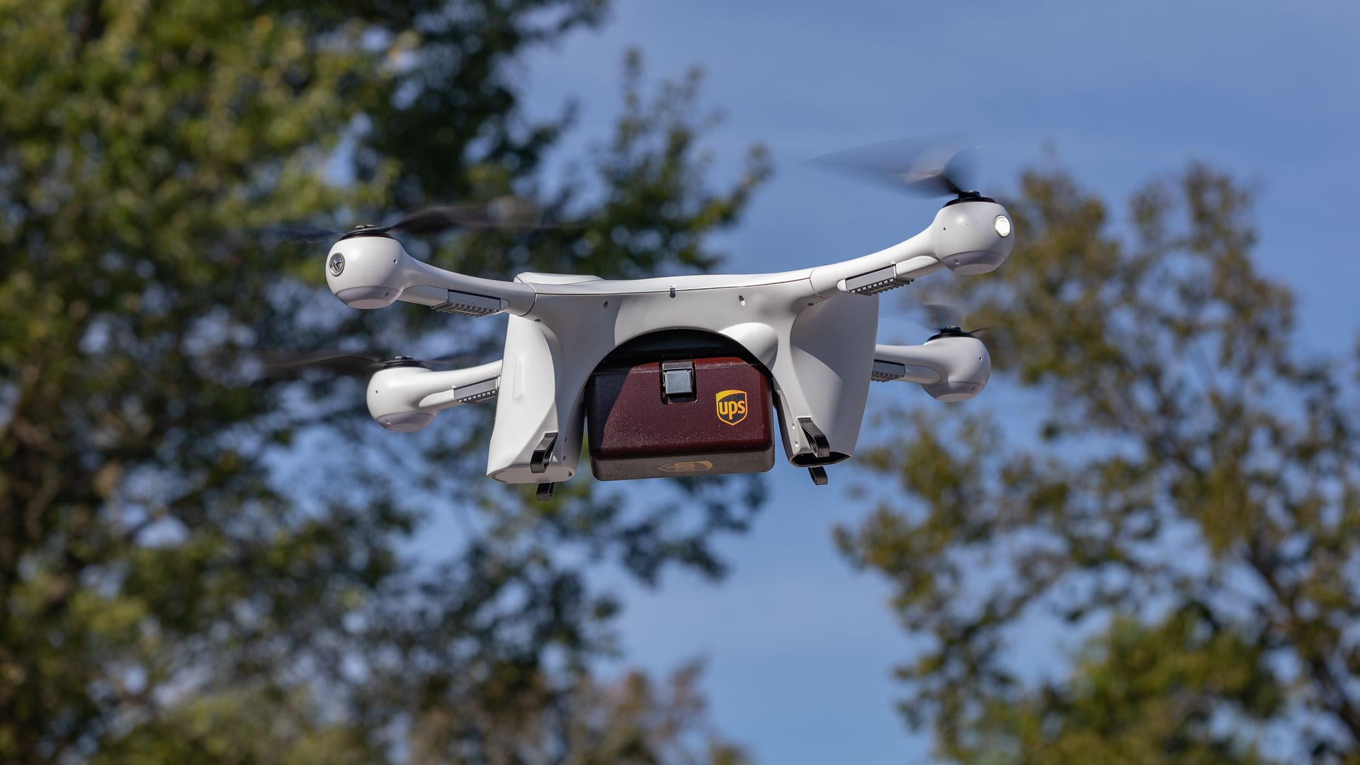 Image of a drone carrying a small UPS package
