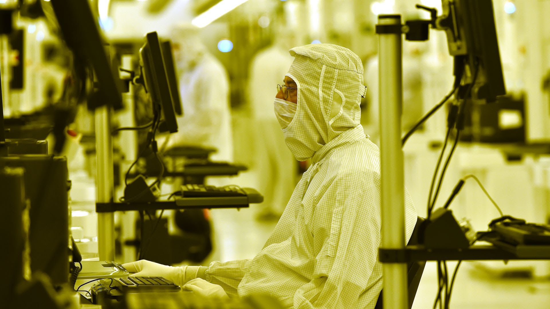Worker in mask and suit works in factory