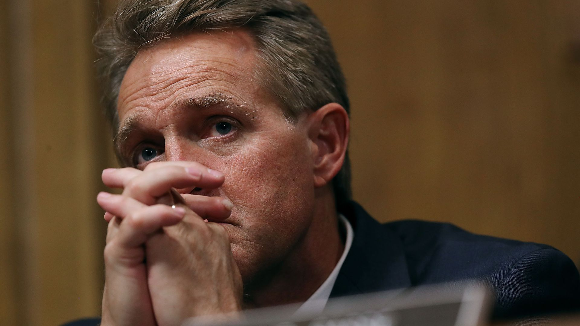 Jeff Flake with his hands intertwined touching his face.