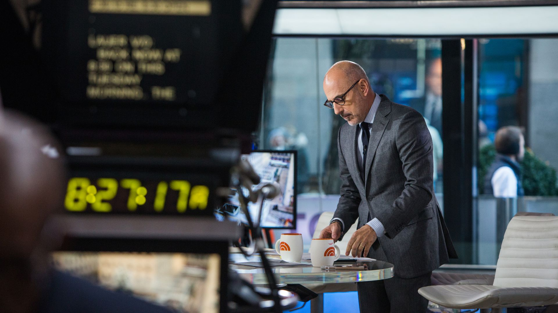 Matt Lauer leans over a table while on set of The Today Show