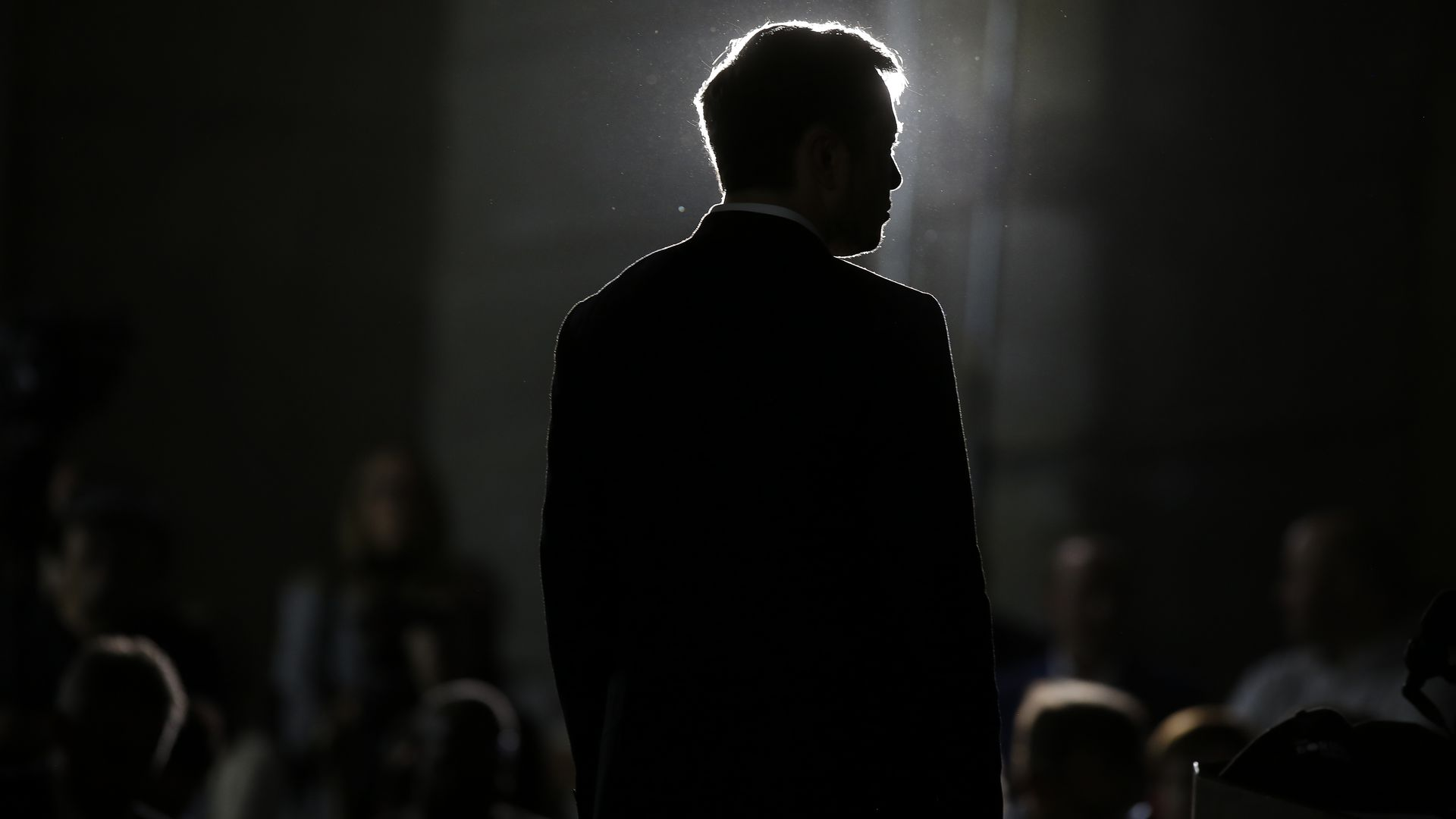 A dark image with the dark silhouette of Elon Musk
