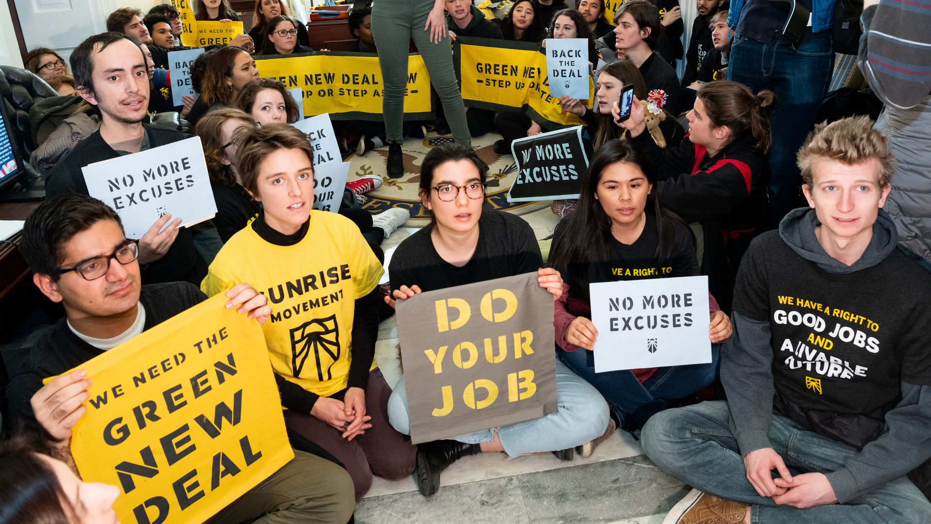 "Youth activists sit with signs that read ""green new deal"" and ""do your job"""