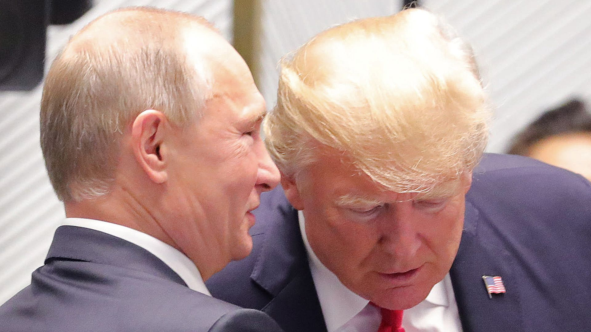 Vladimir Putin whispering to Donald Trump during a meeting of world leaders.