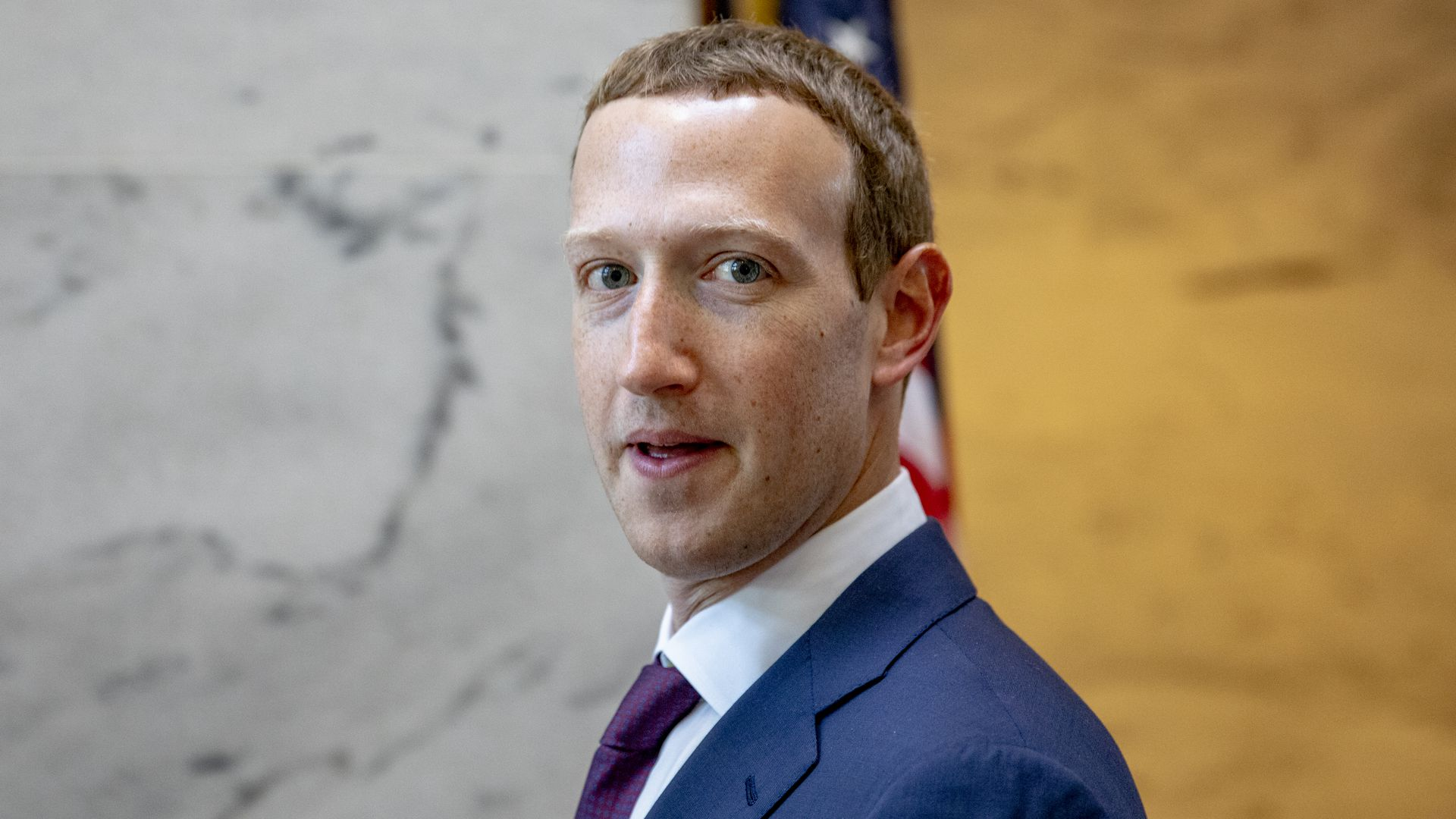 In this image, Zuckerberg's profile is turned away from the camera as he faces it head-on. He's wearing a suit