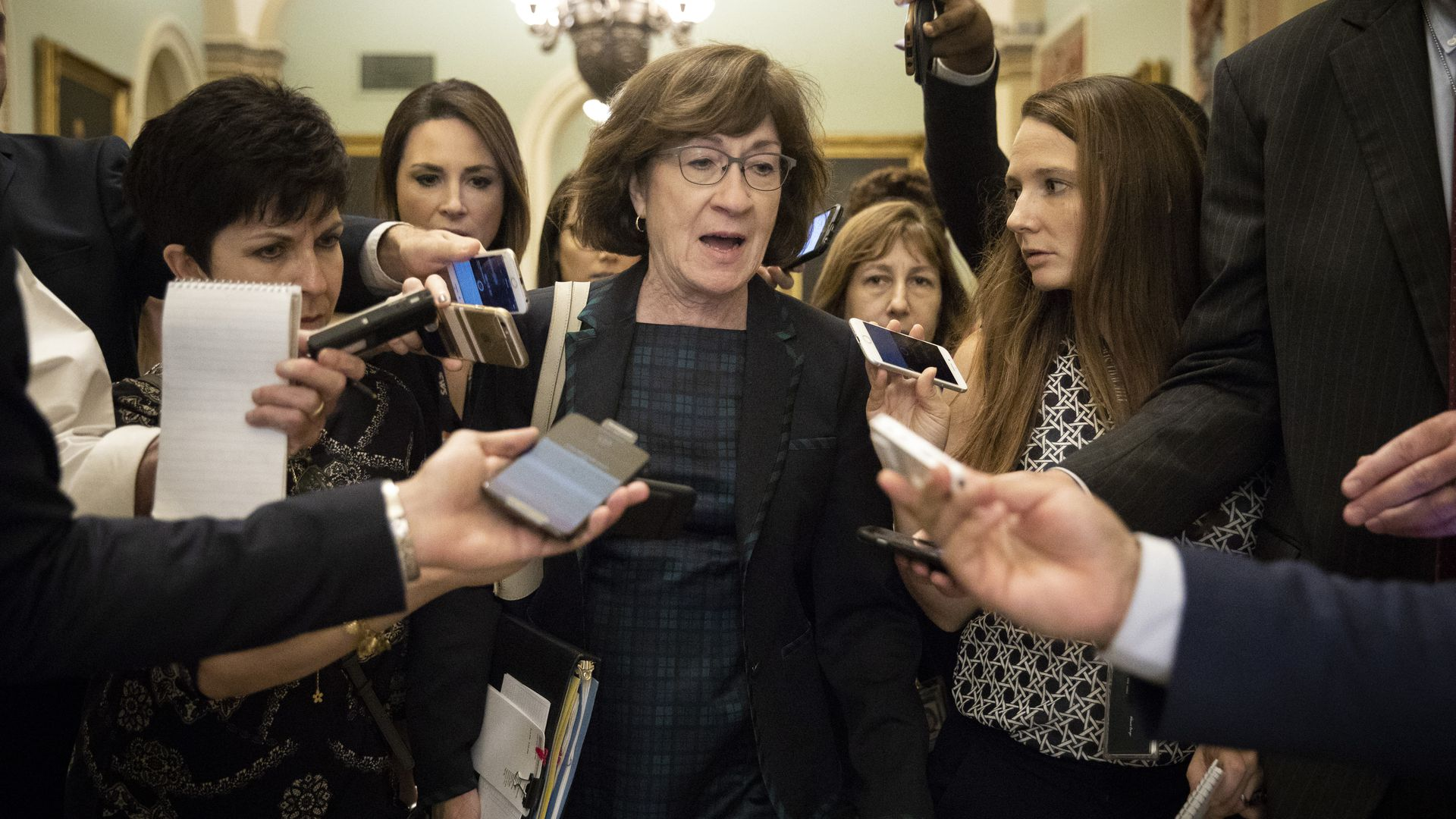 Susan Collins surrounded by reporters on Capitol Hill