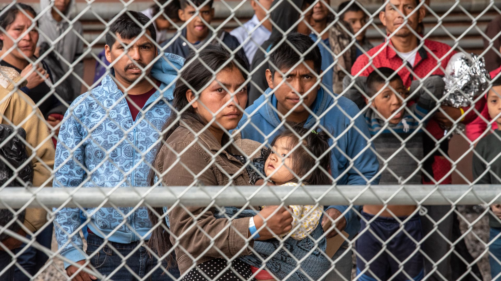 Migrants are gathered inside the fence of a makeshift detention center