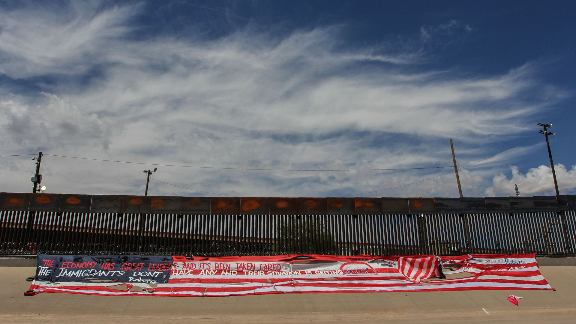 This image shows a larger horizontal American flag in front of a wall at the southern border.