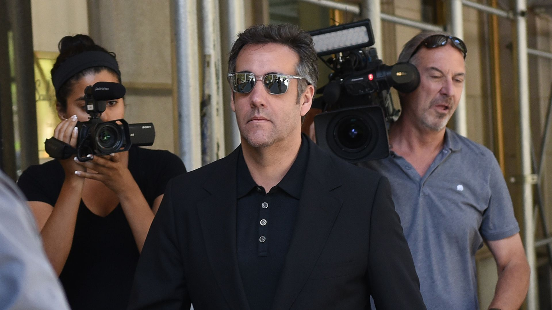 Michael Cohen wearing sunglasses and surrounded by paparazzi