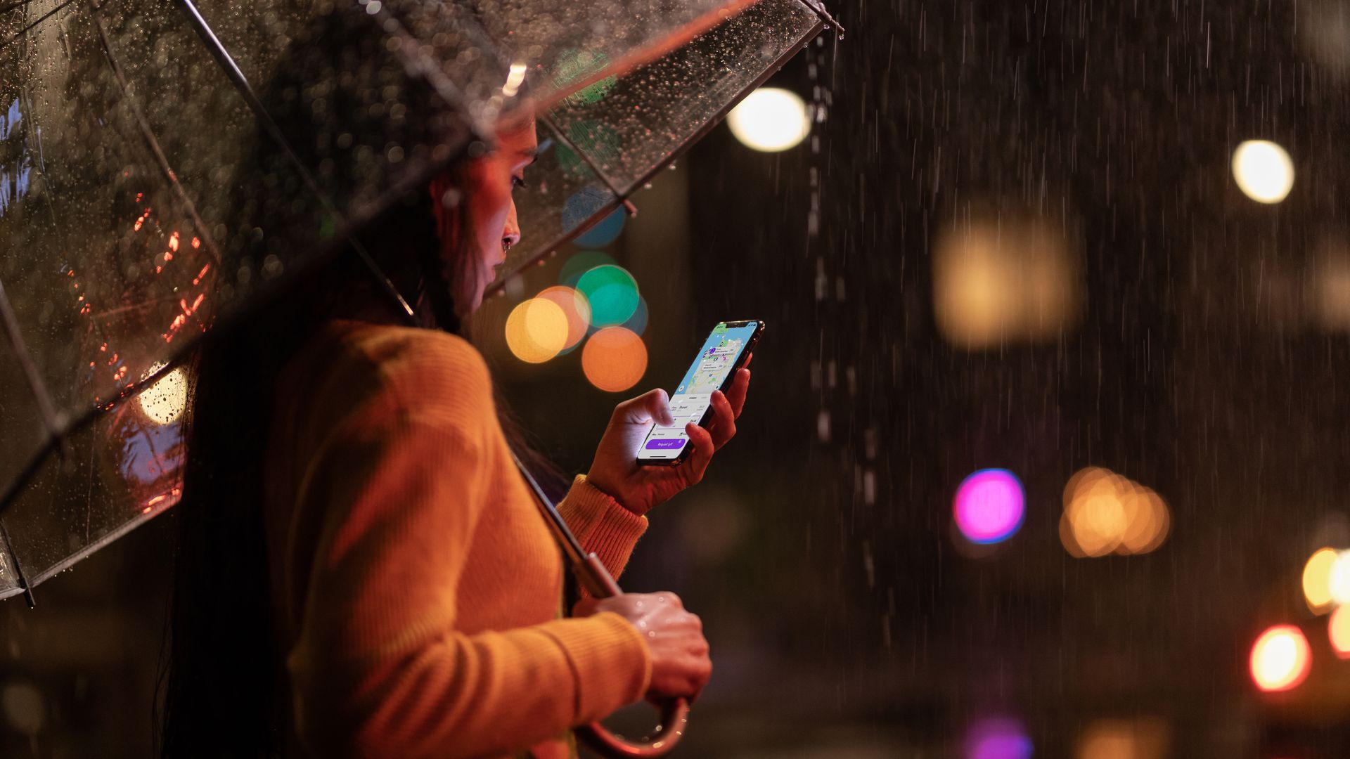 A woman holding an iPhone Xs Max in the rain
