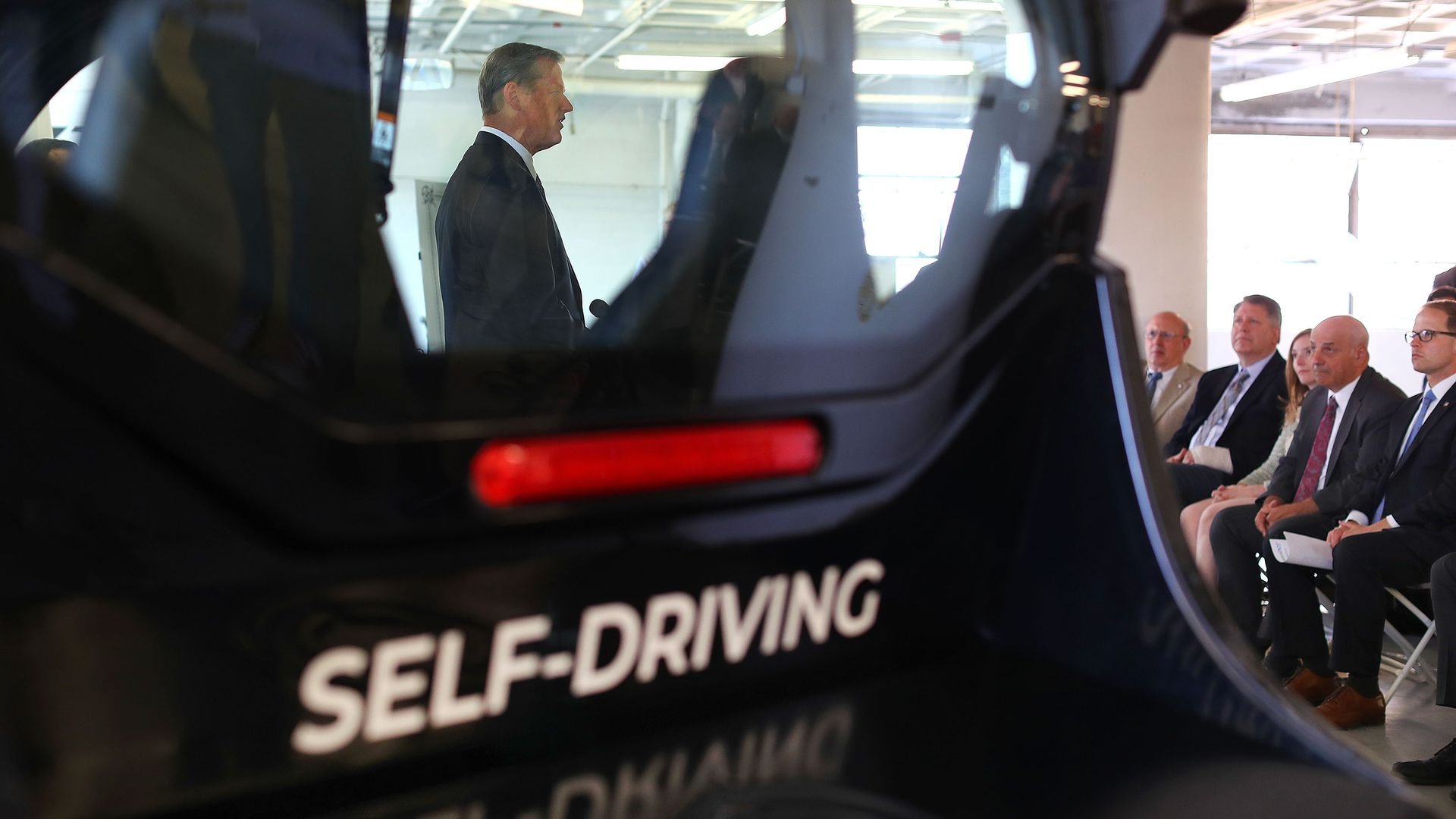 "In this image, the words ""self-driving"" are seen on the back of a black car."