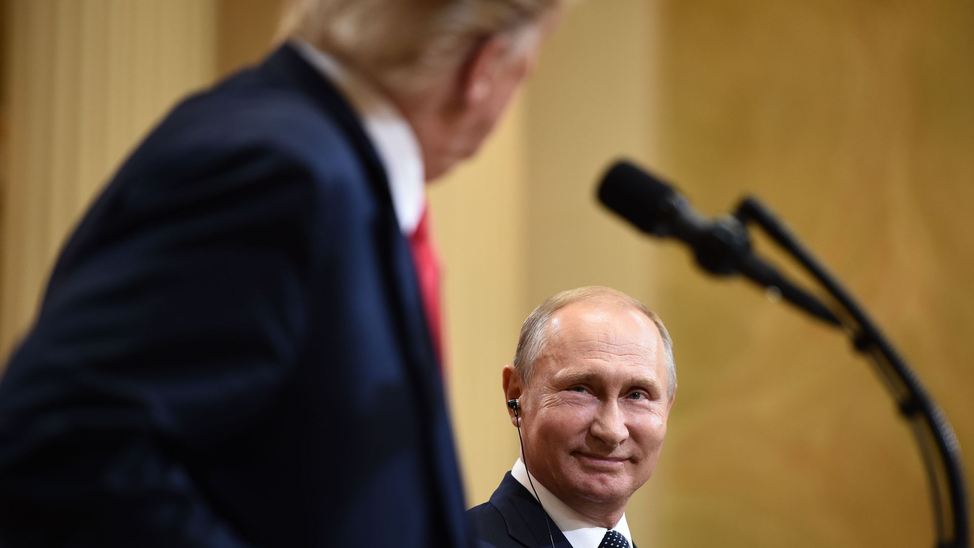 Vladimir Putin smiles at Trump, who looks at him over his podium.