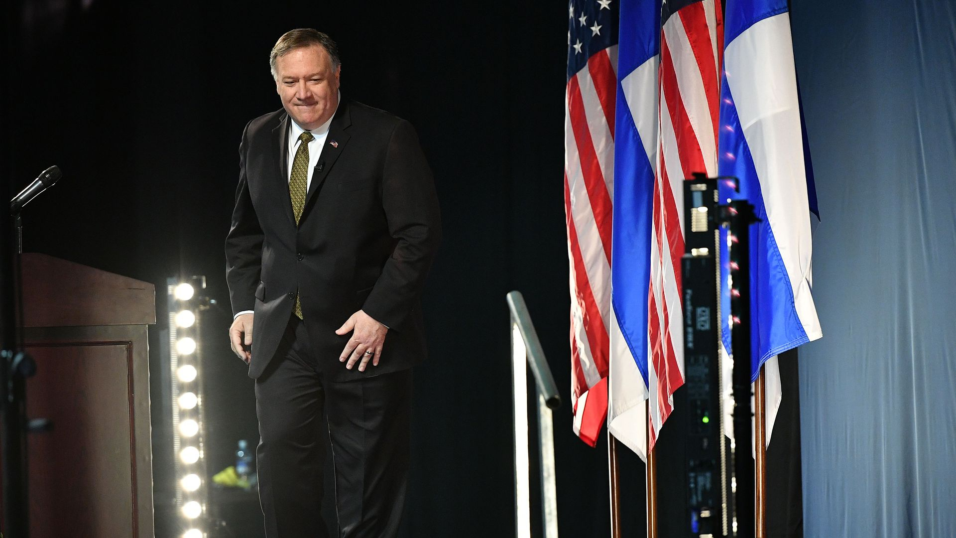 In this image, Pompeo steps down from the stage at the Arctic Council. A row of American and Finland flags are next to him.